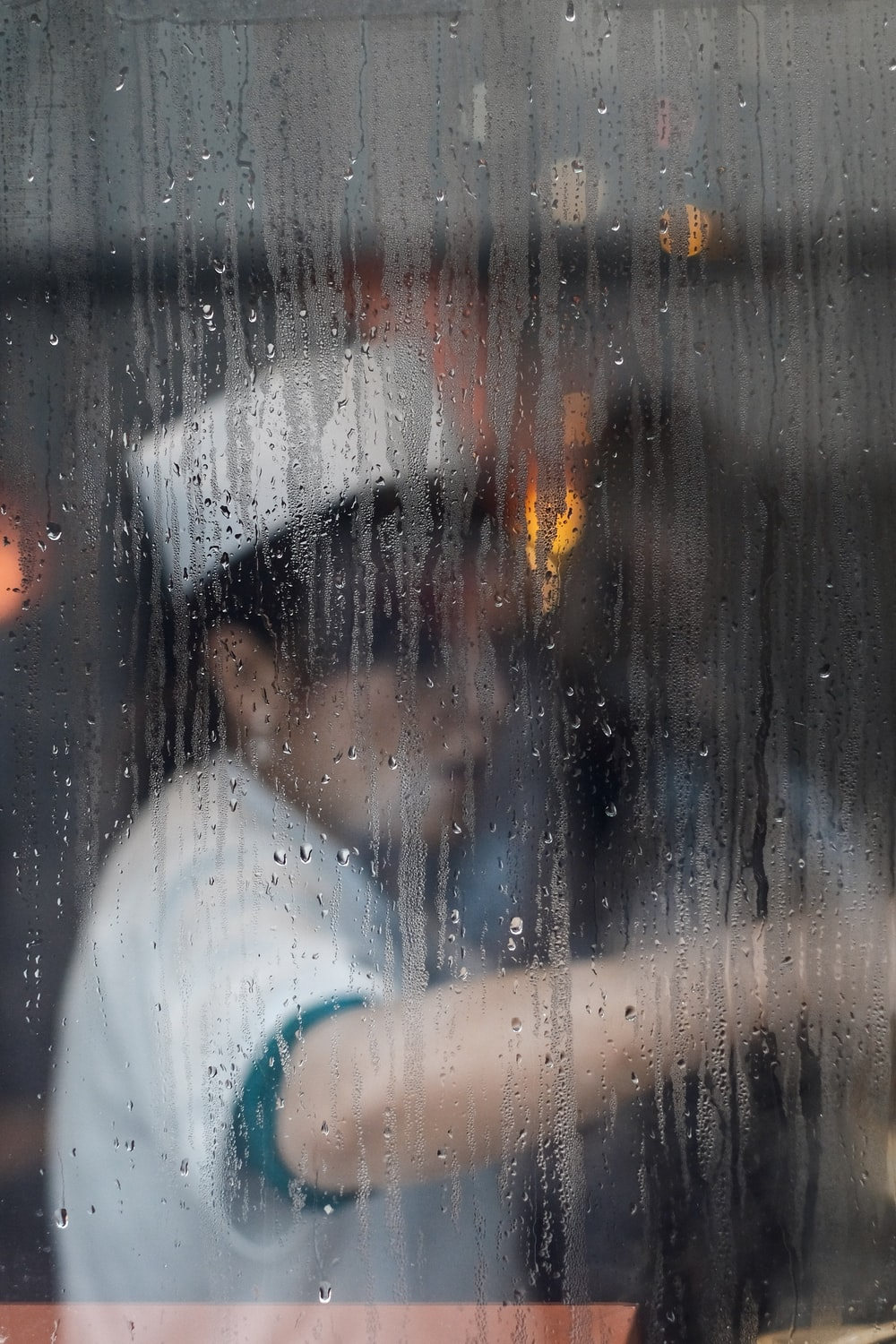 A cook at work seen through a rainy window