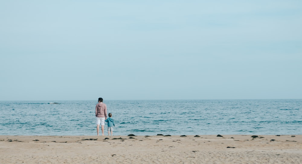 man and toddler standing on shore