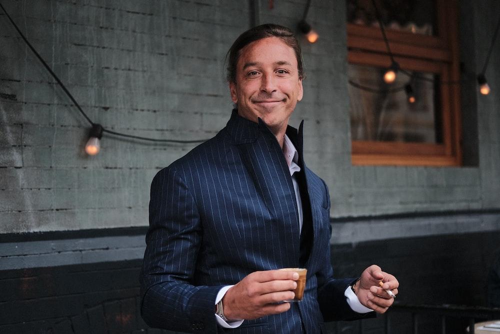 man wearing black suit holding brown mug near black string lights