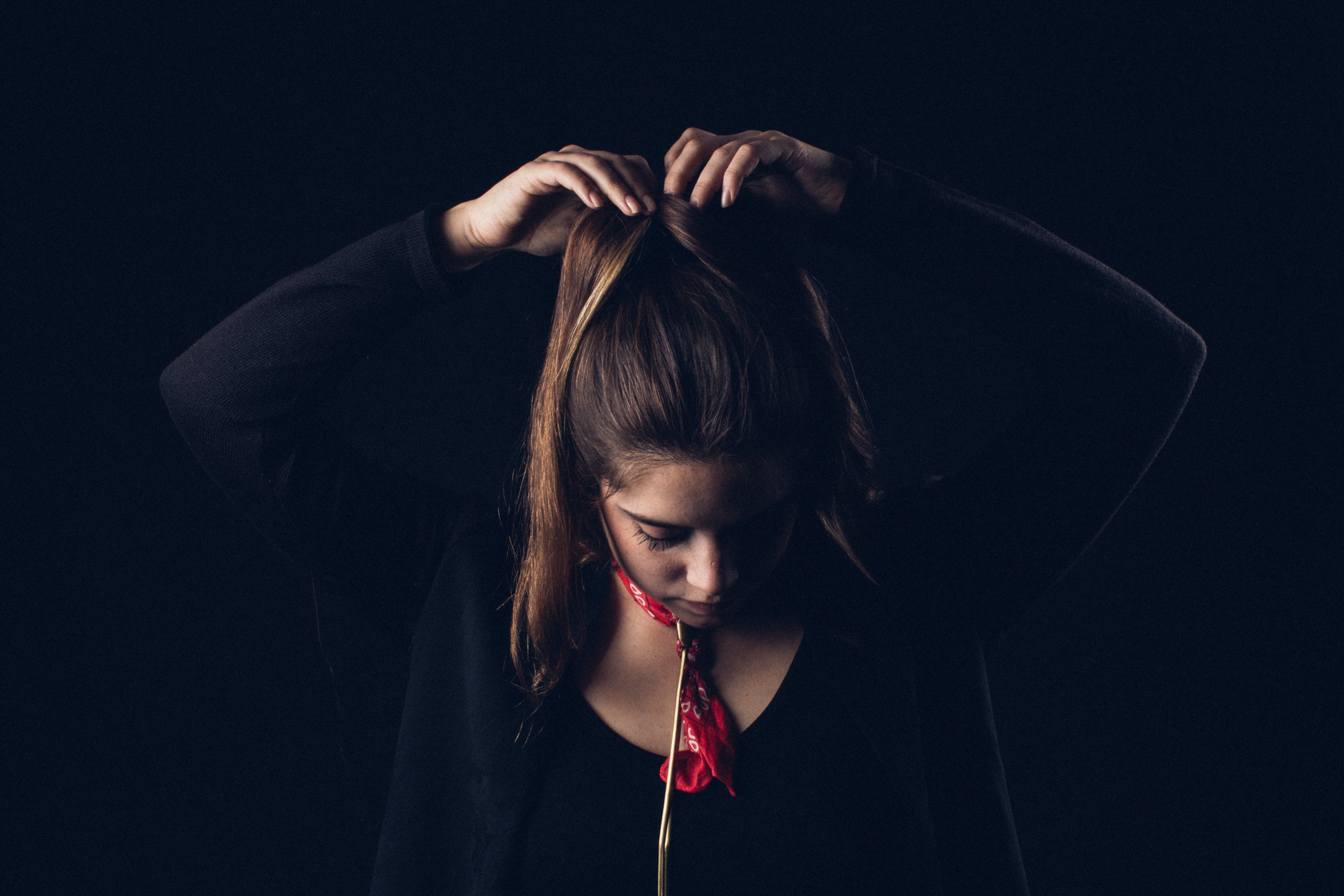 A woman wearing a red bandana and black shirt fixes her ponytail against a black background
