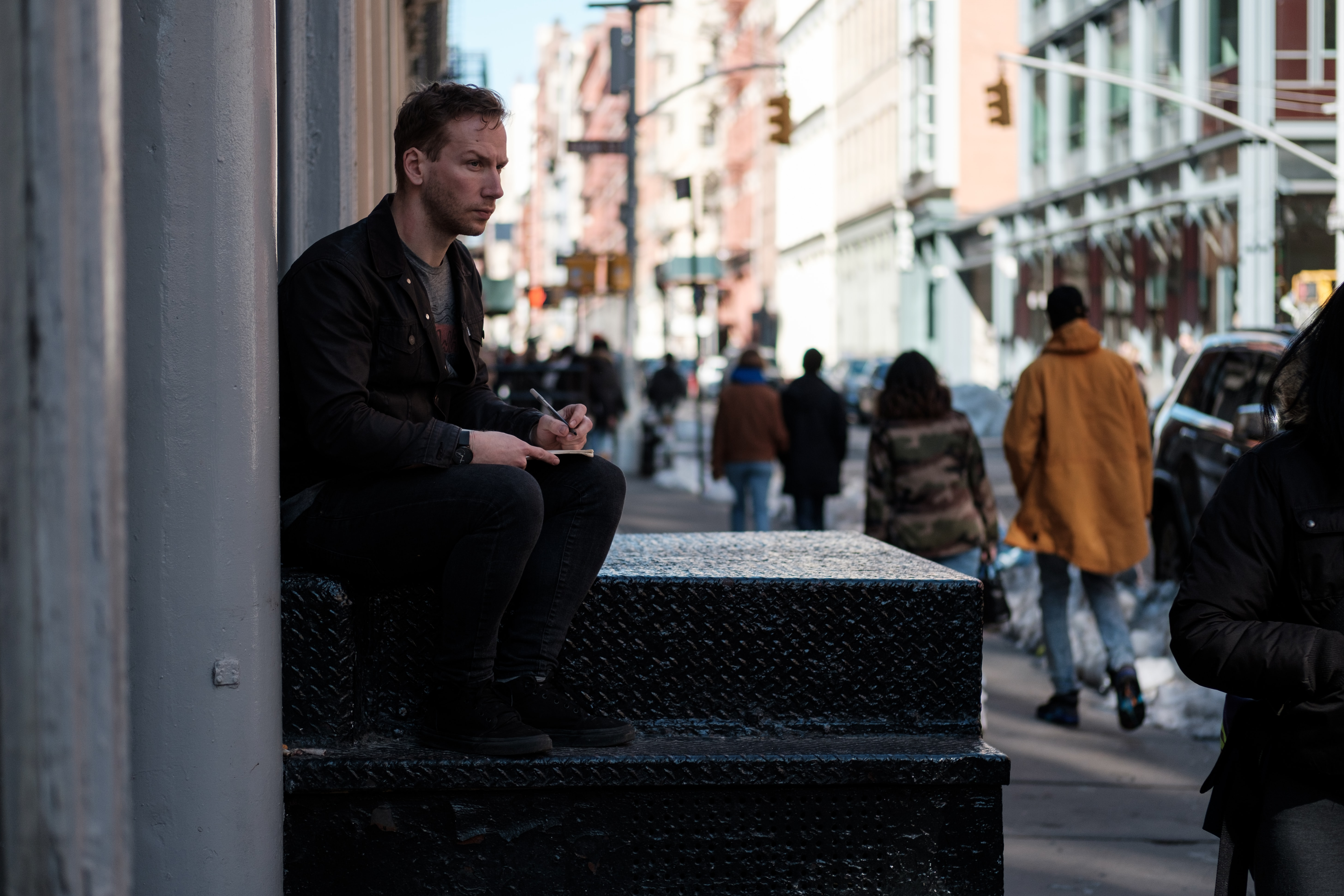 A man with a sketchpad sitting on stairs on a sidewalk