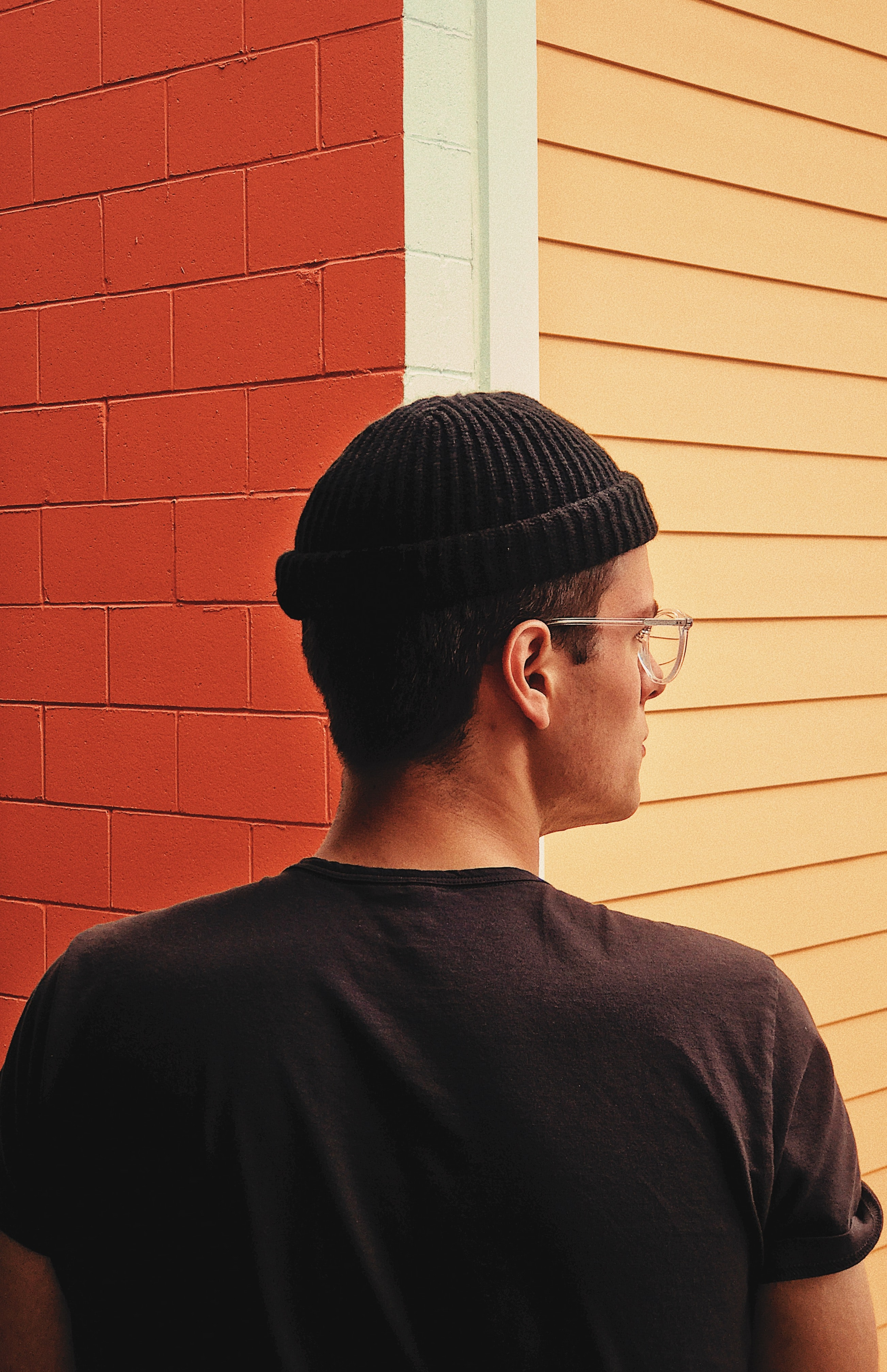 A mixed race mal wearing glasses, looking to the right while standing in front of a building corner.