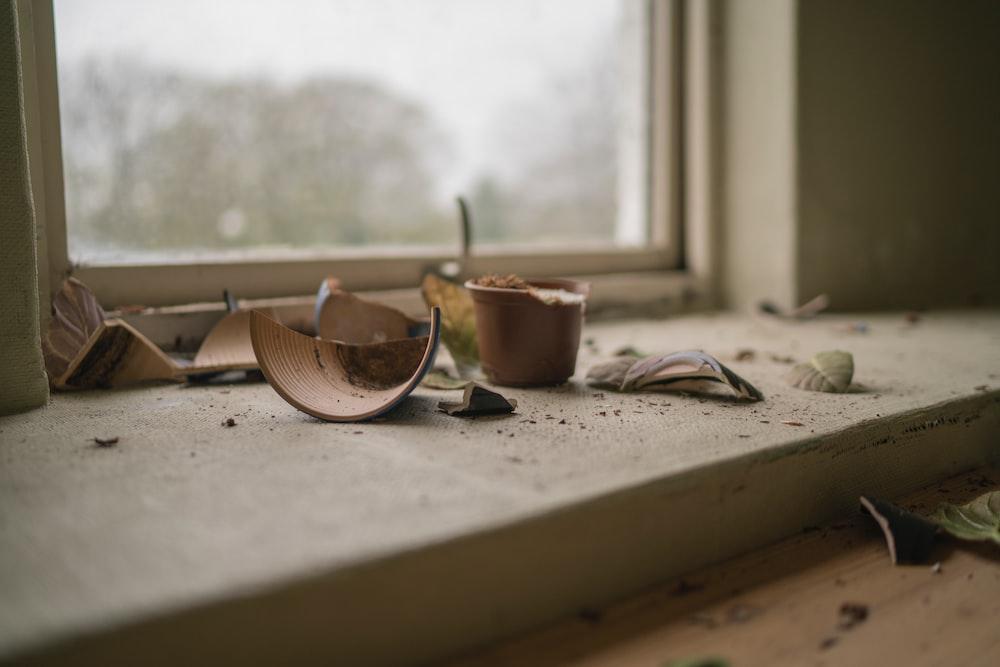 A shattered flowerpot on a windowsill