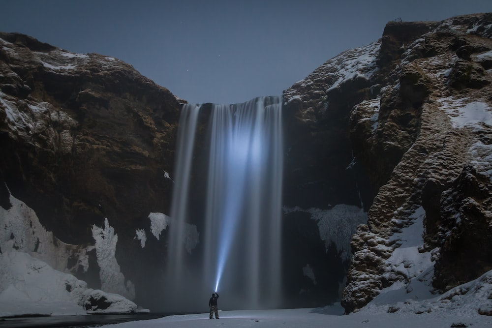 man standing in front of the waterfalls