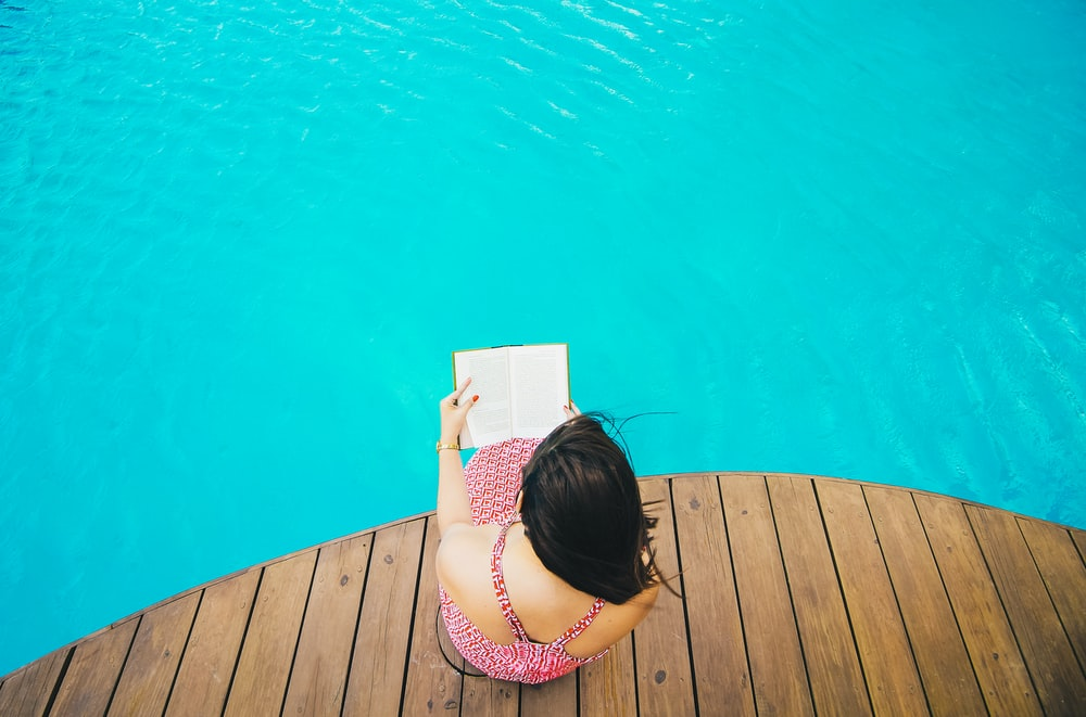 woman sitting on poolside dock while riding book