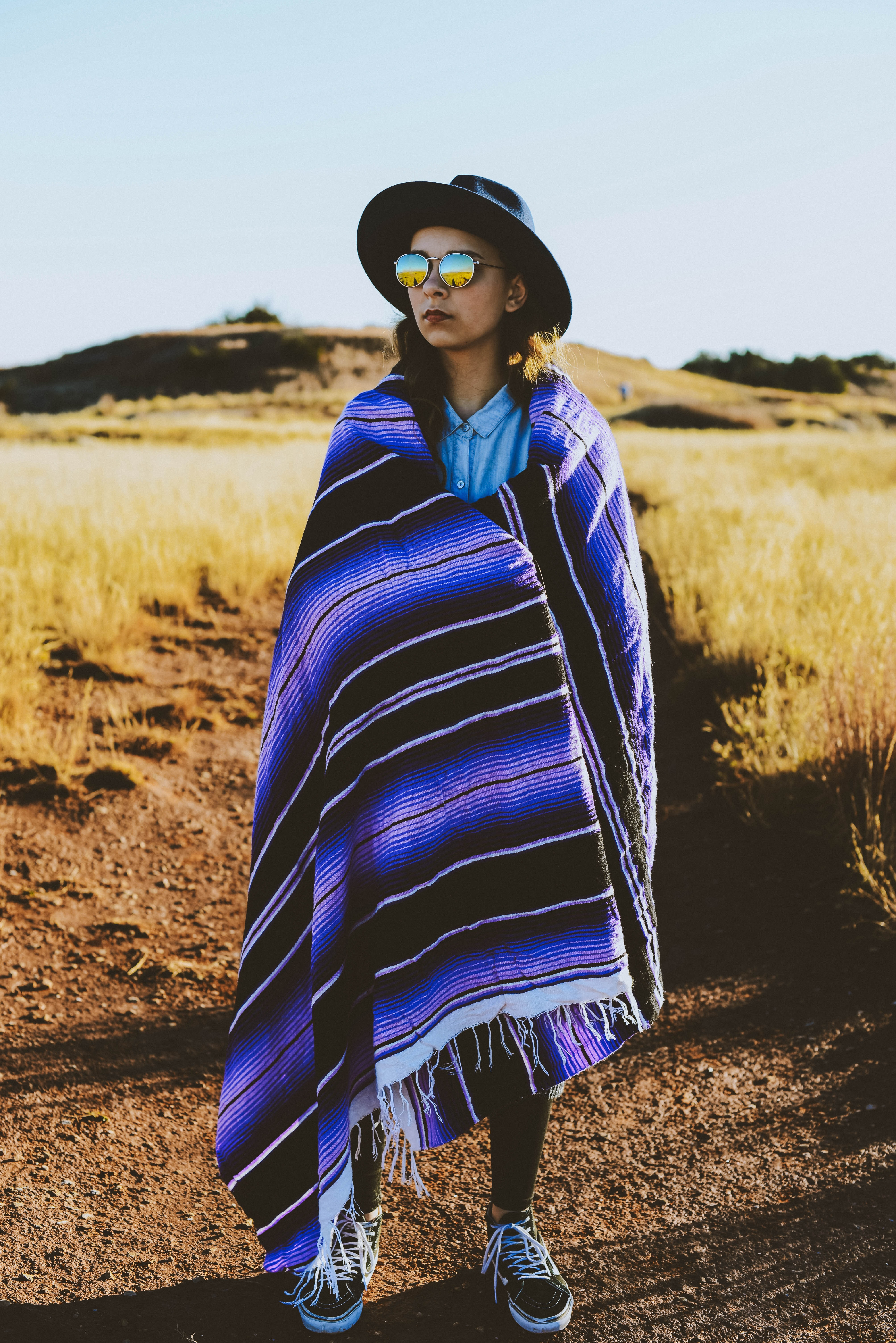 A woman in sunglasses and a hat stands on a desert path wrapped in a blanket