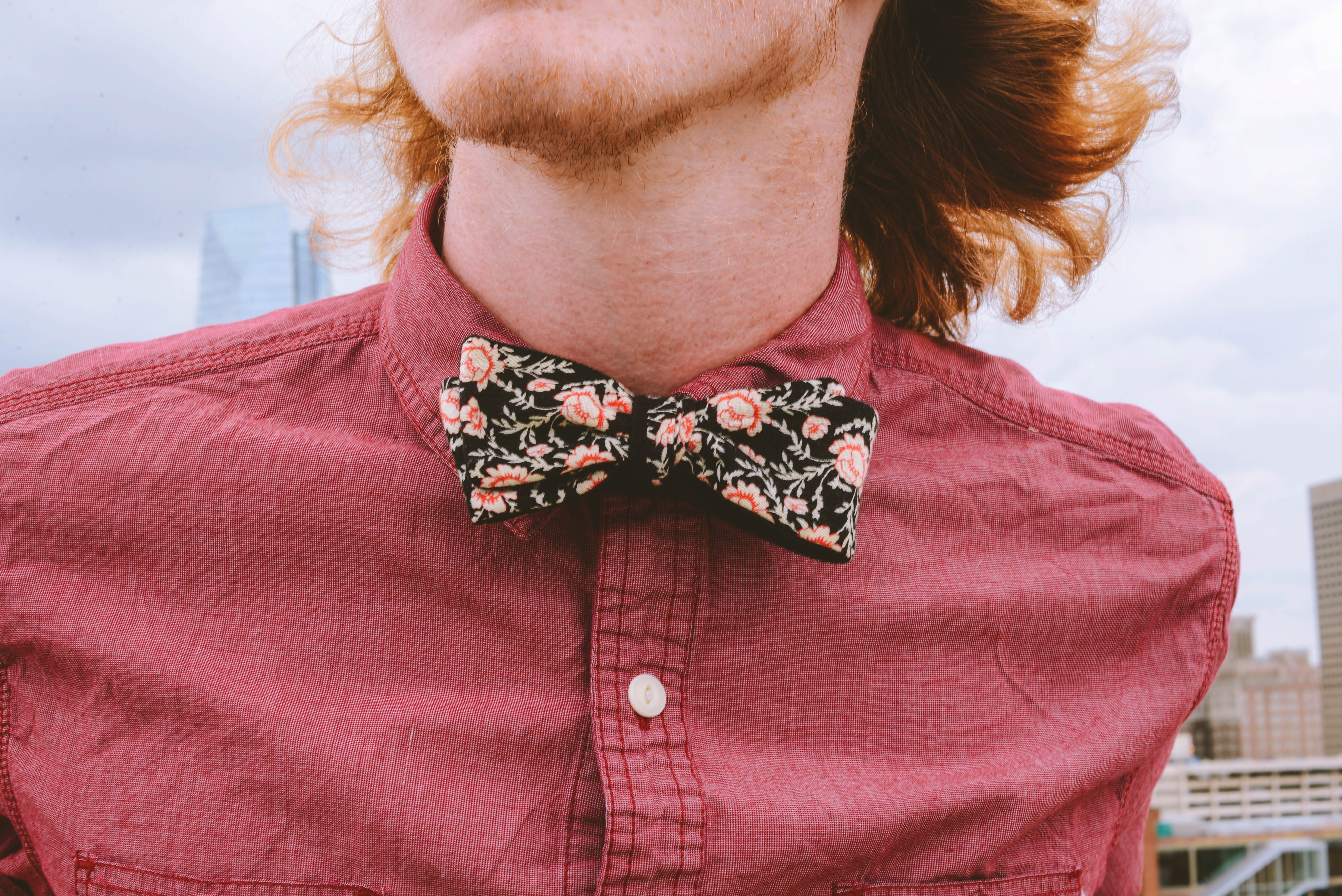 closeup photography of person wearing floral bowtie and red dress shirt
