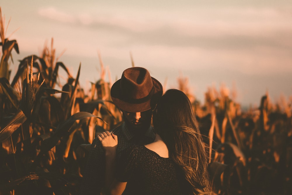 man and woman hugging each other in the field