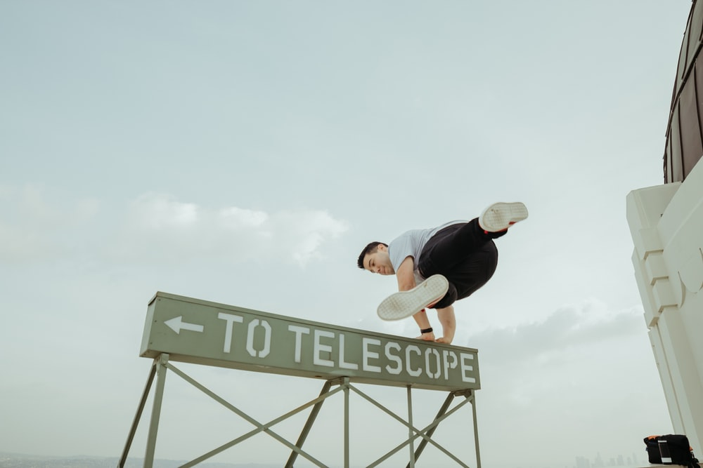 man jumping over to telescope signage