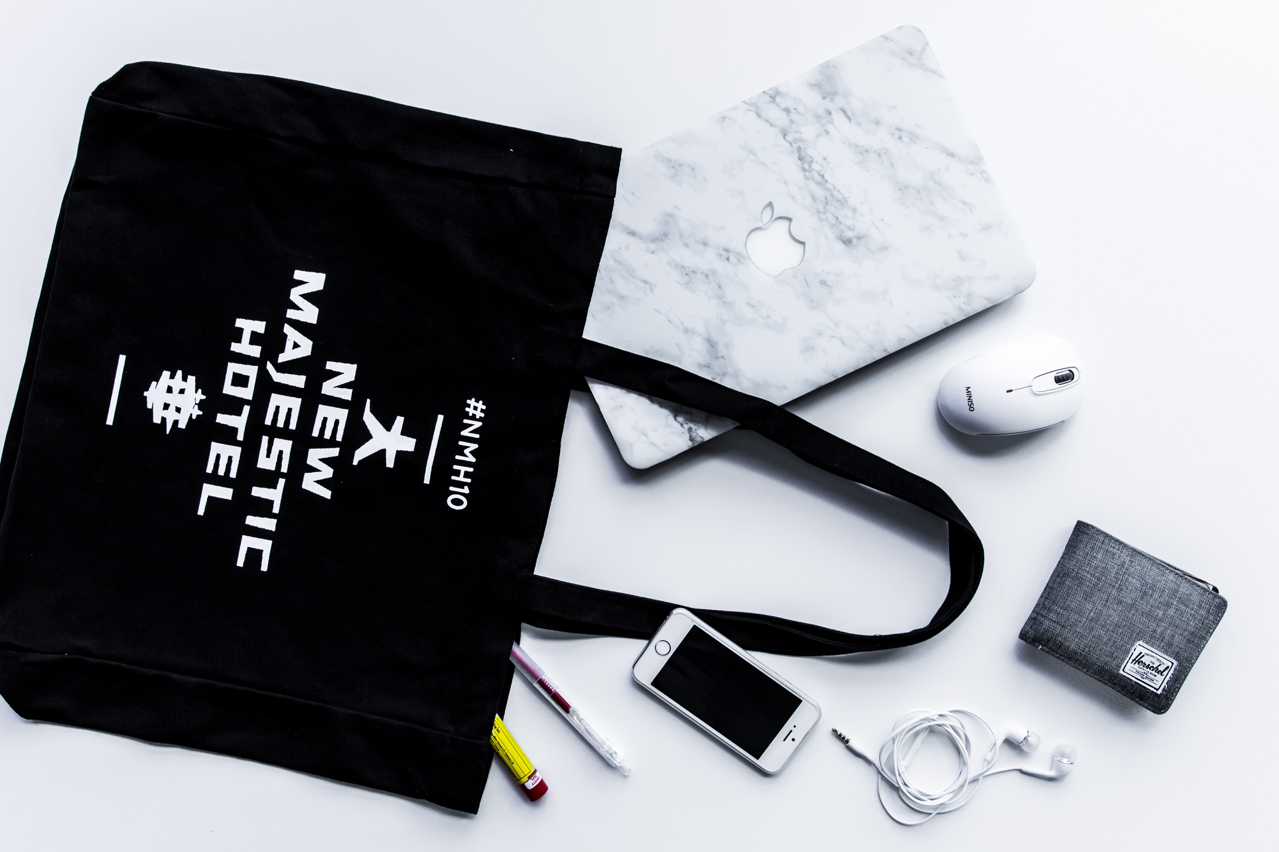 flat lay photography of tote bag beside iPhone and wallet