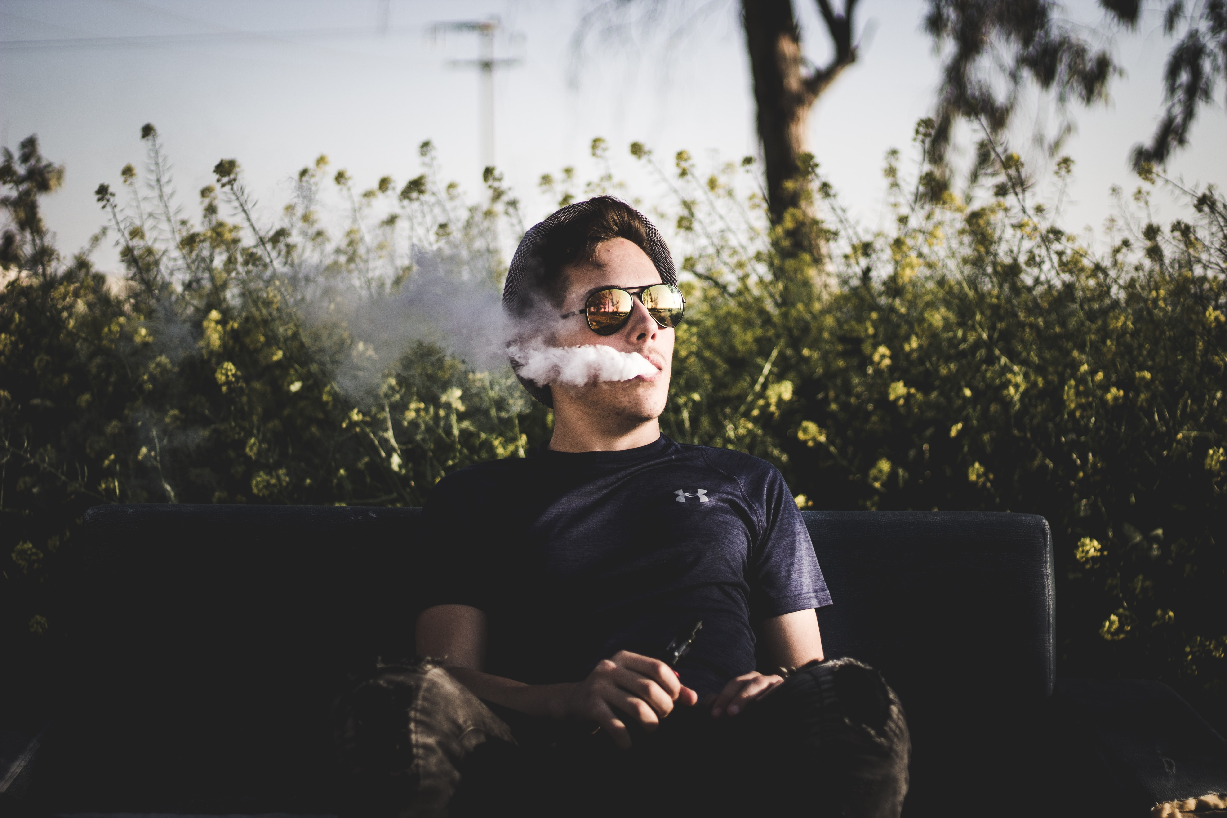 Hipster man in sunglasses vaping and blowing smoke from his mouth