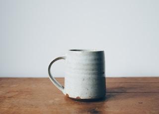 white ceramic mug on wooden table top