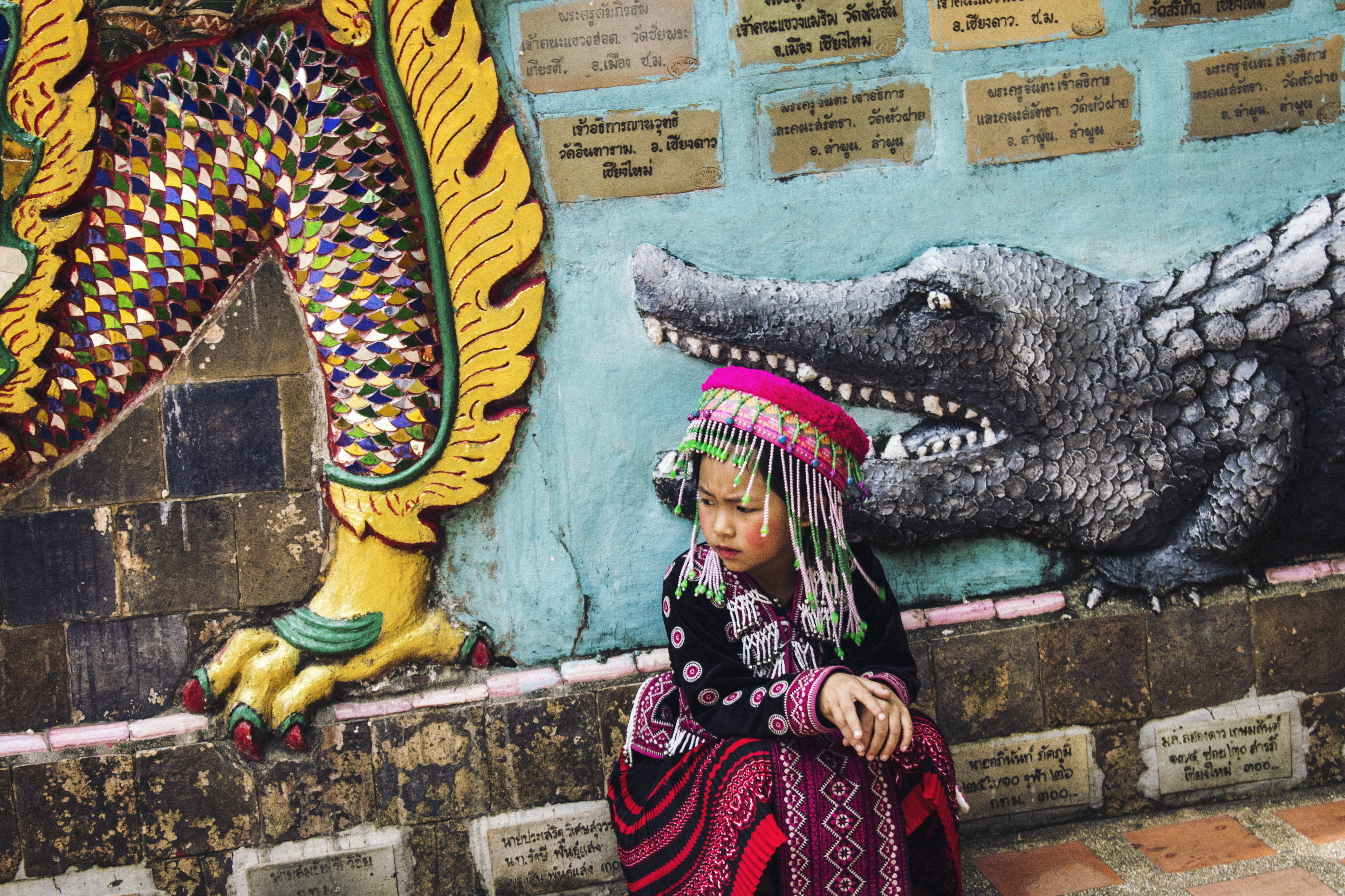 A child wearing a headdress in front of a wall of cultural imagery in Doi Suthep