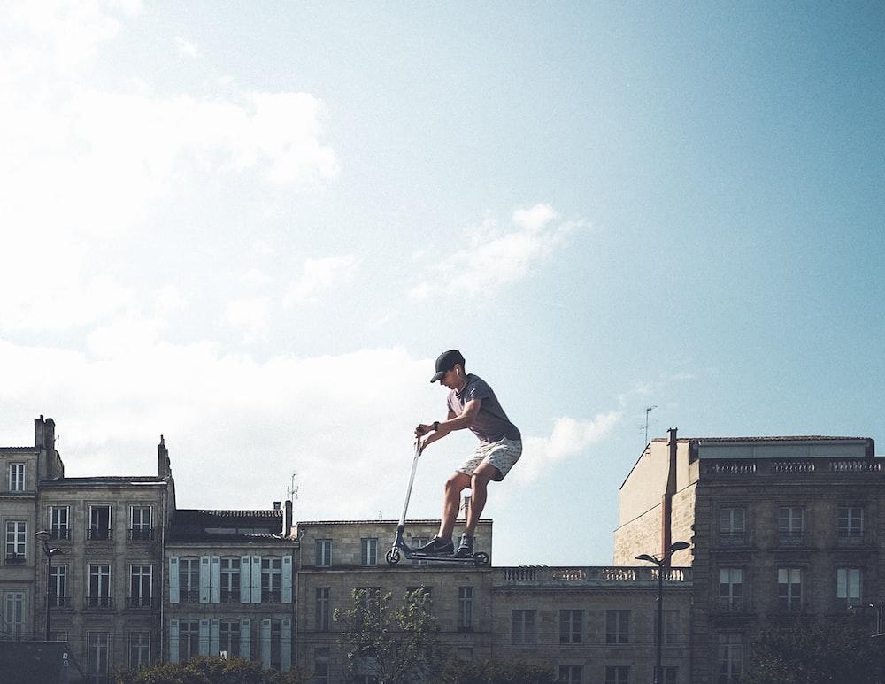 man riding on black kick scooter