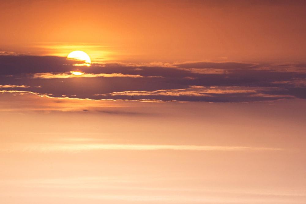 orange sun behind clouds