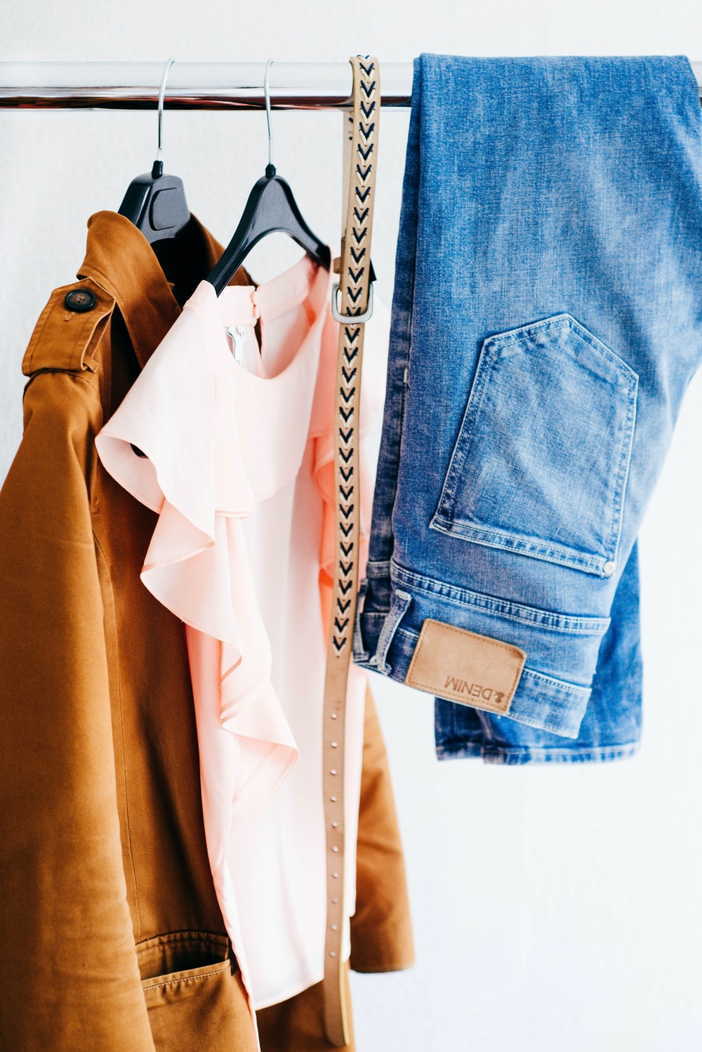 Women's shirts, jeans, and belt hanging on a clothing rack