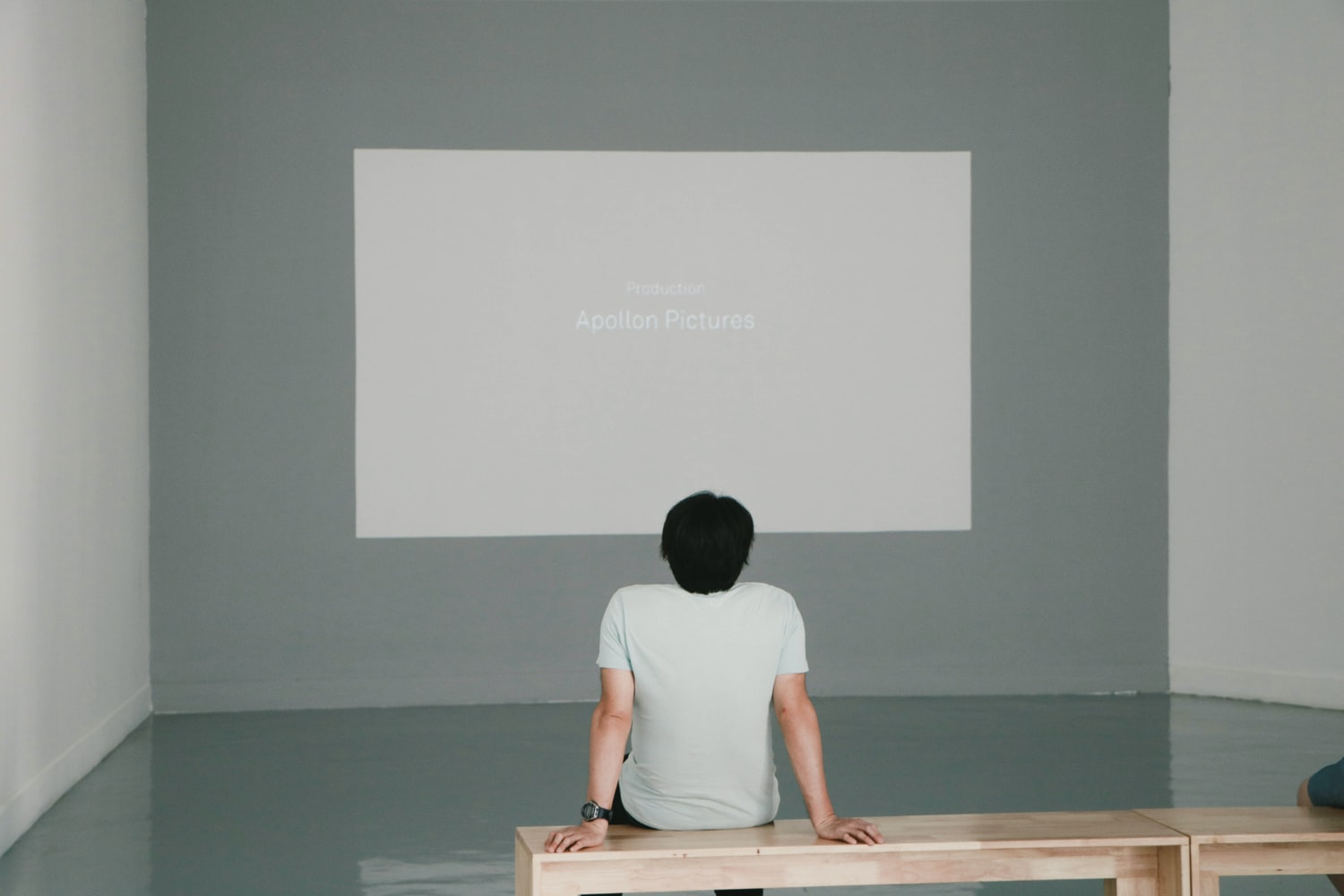 a man sitting on the table, in front of the projector screen