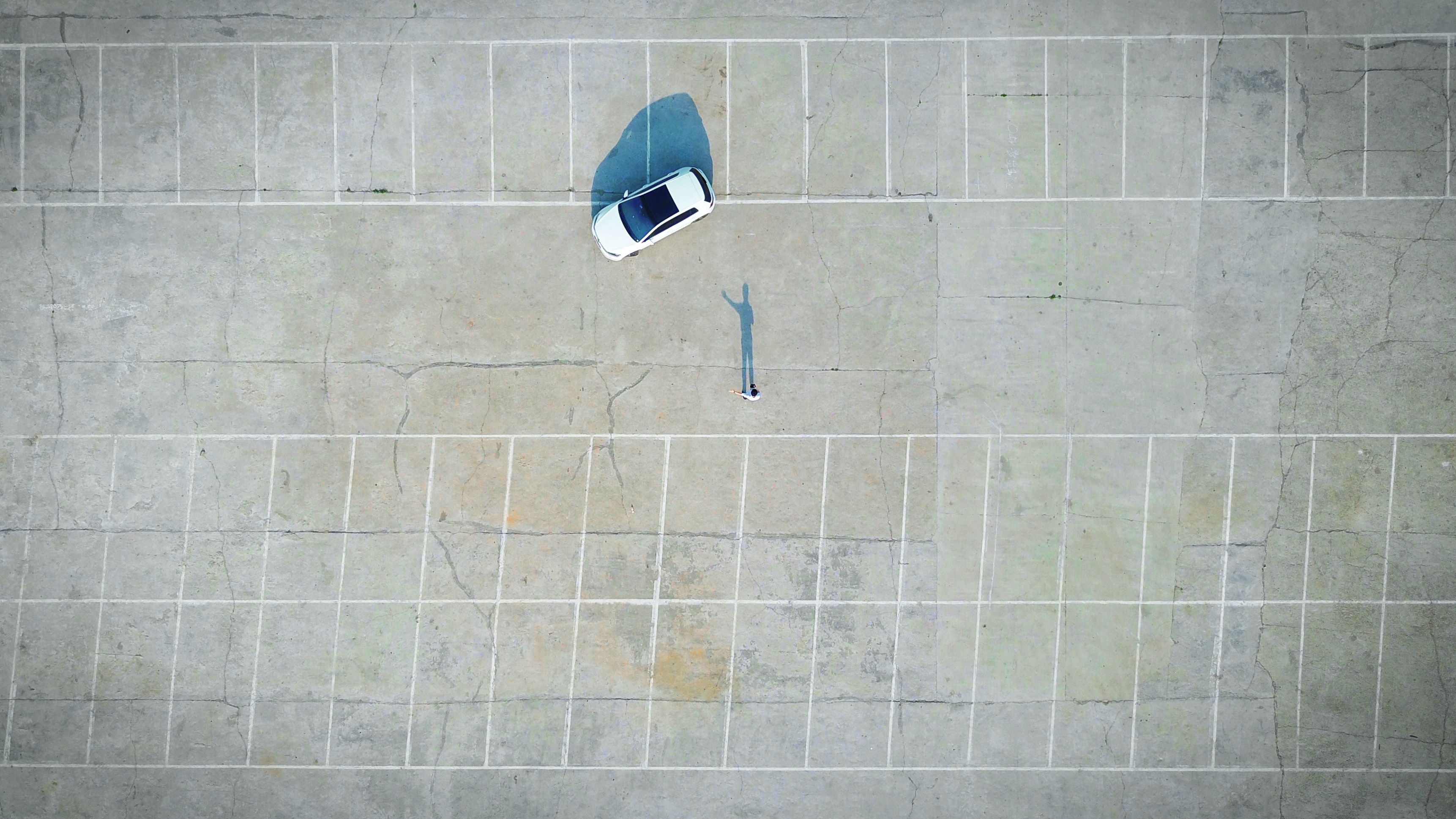 A drone shot of a lone person near a white car in a parking lot