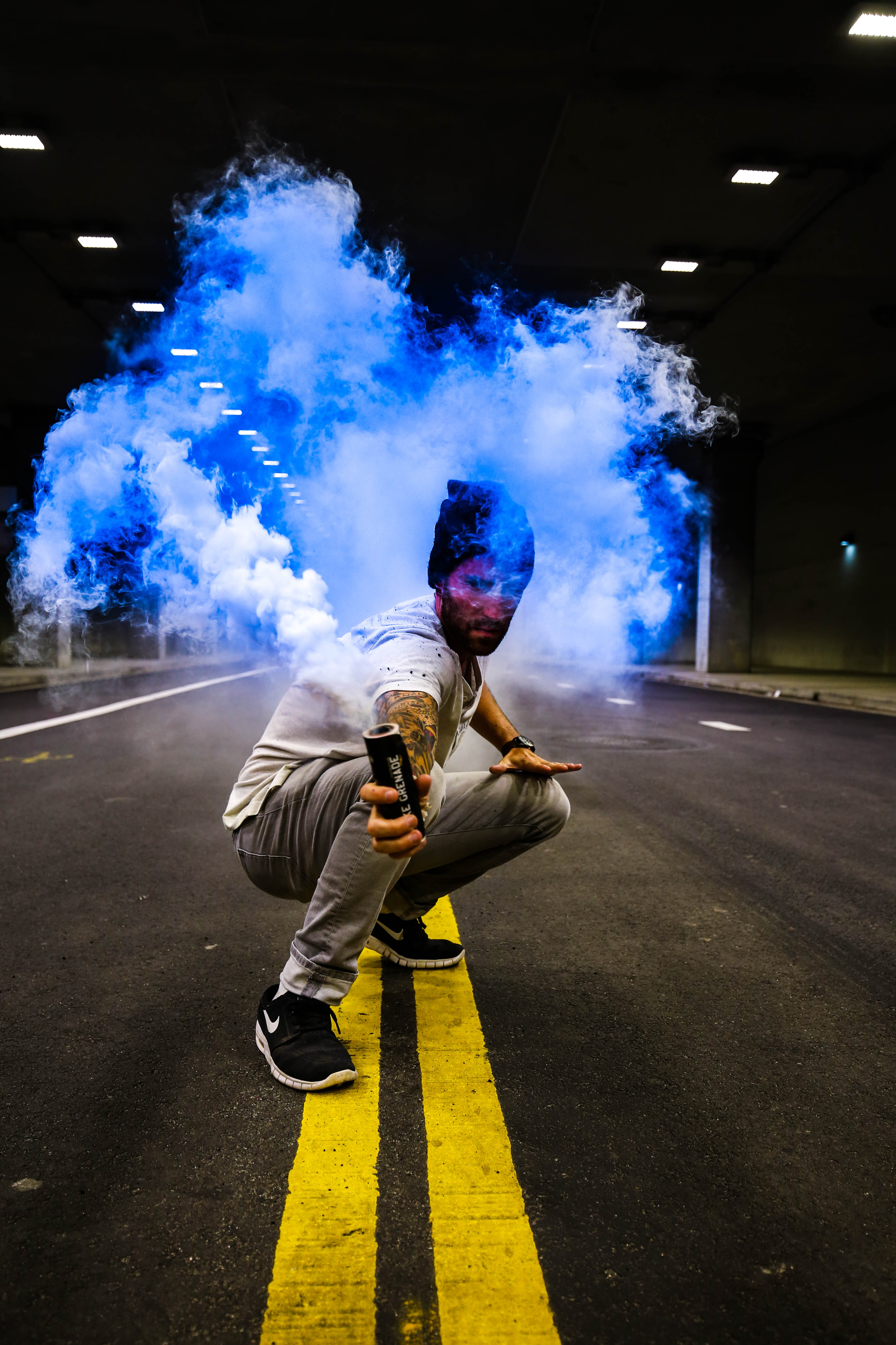 Person crouching in the street holding a blue smoke grenade