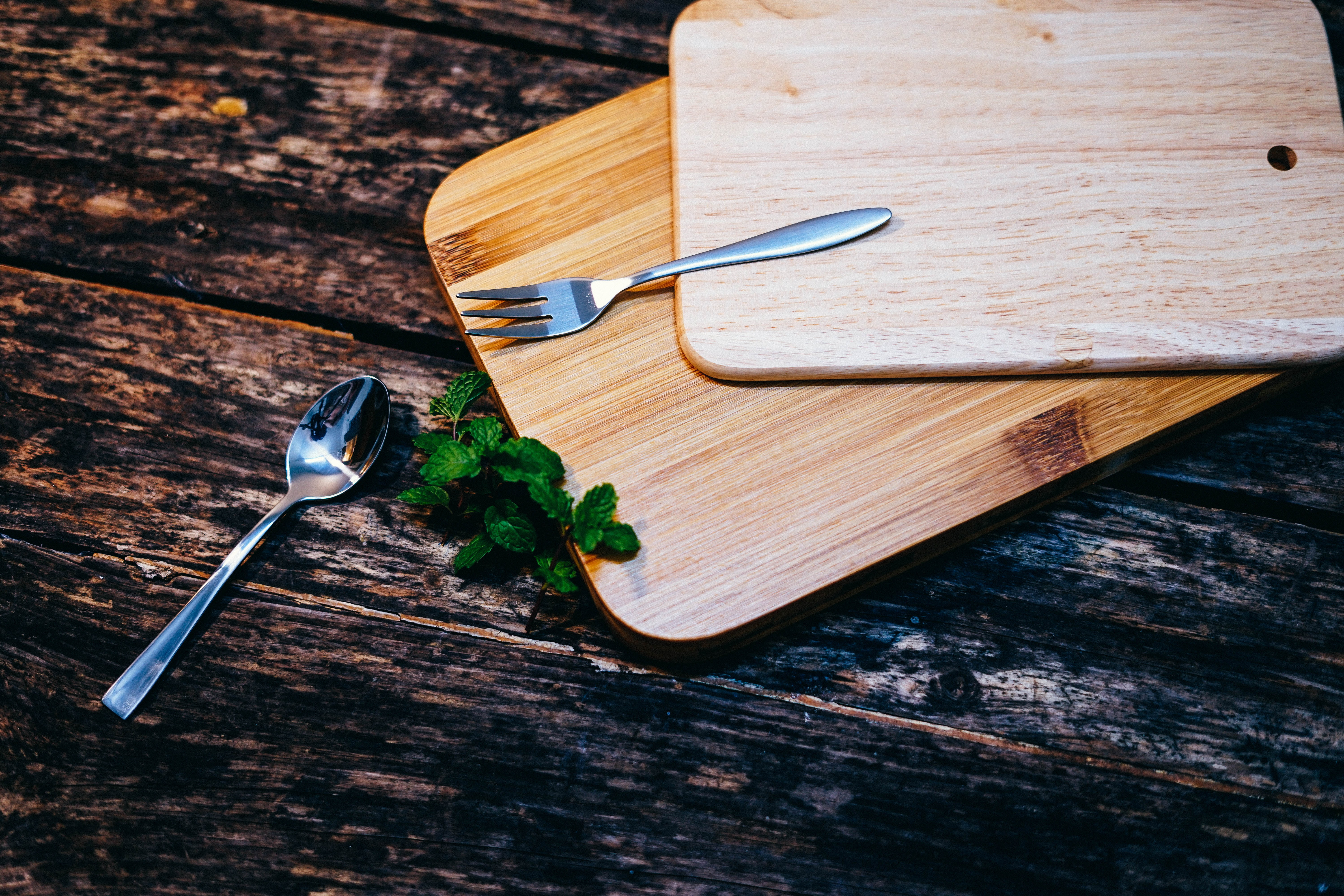 Two wooden chopping boards on top of each other beside leaves of mint and a metal spoon and fork