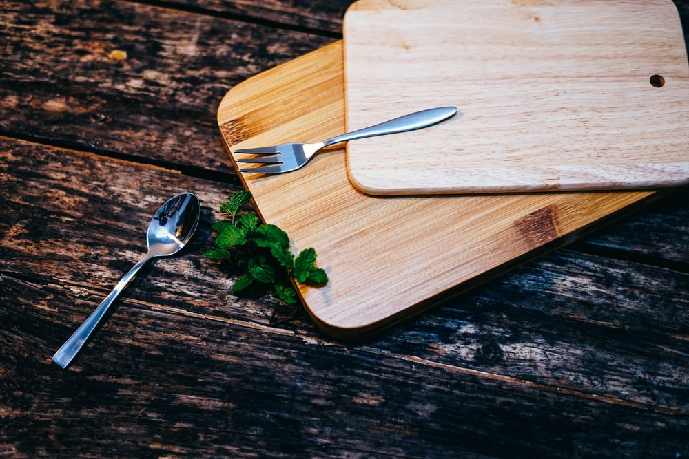 stainless steel spoon and fork on brown wooden board