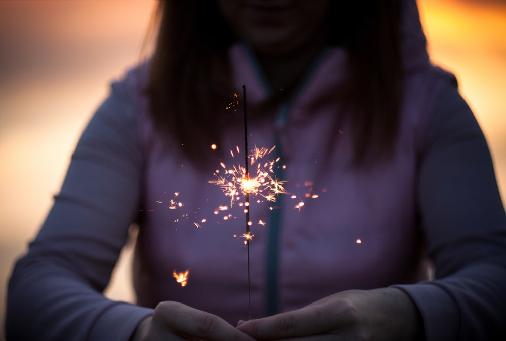 A woman in a hoodie holds a lit sparkler in her hands