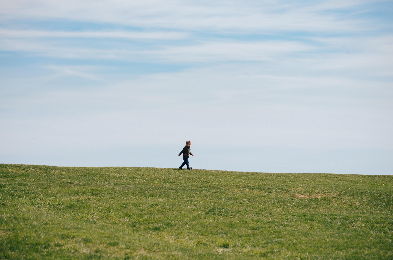 child walking on green grass field