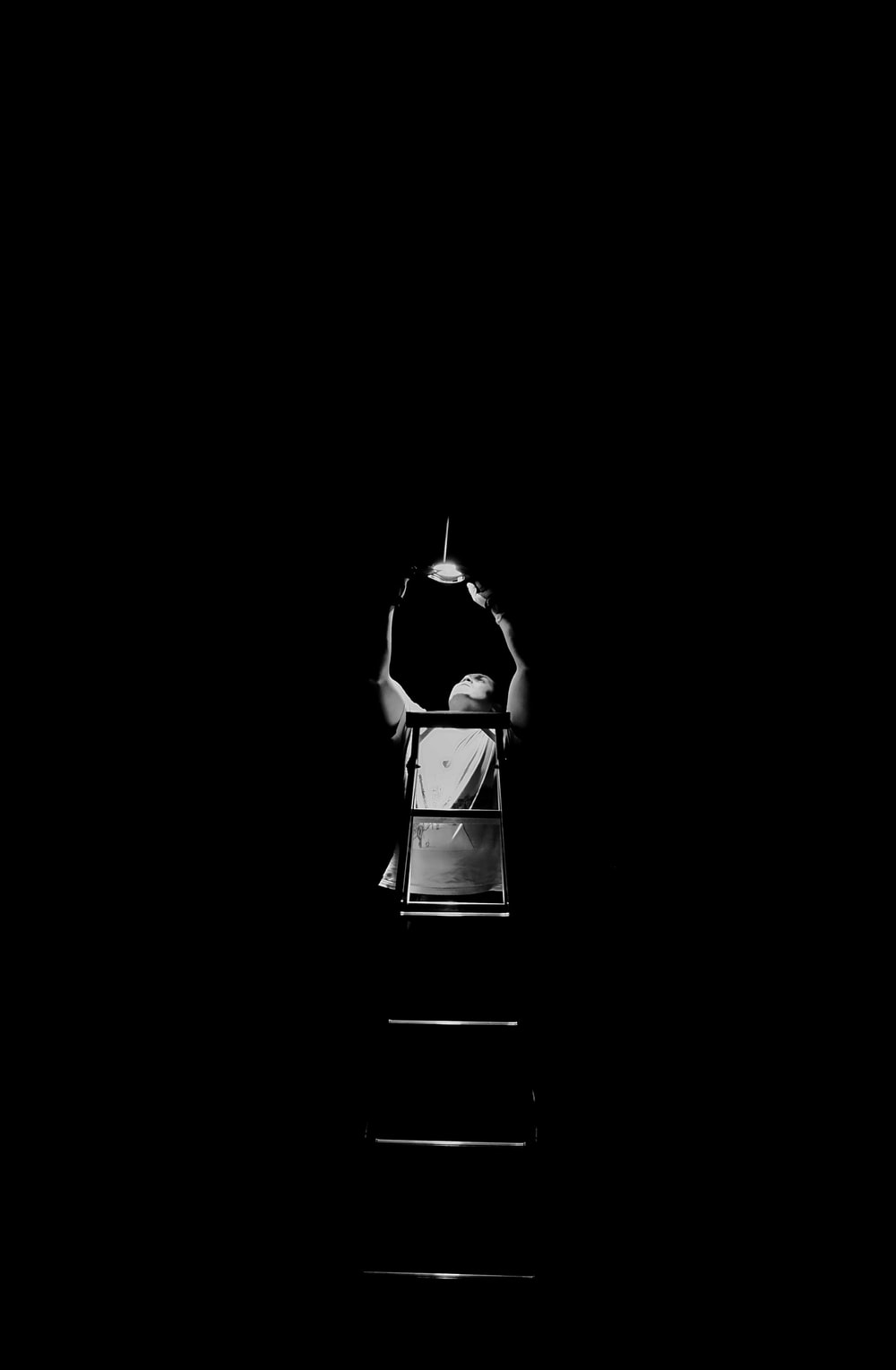 grayscale photography of man climbing ladder fixing the lights