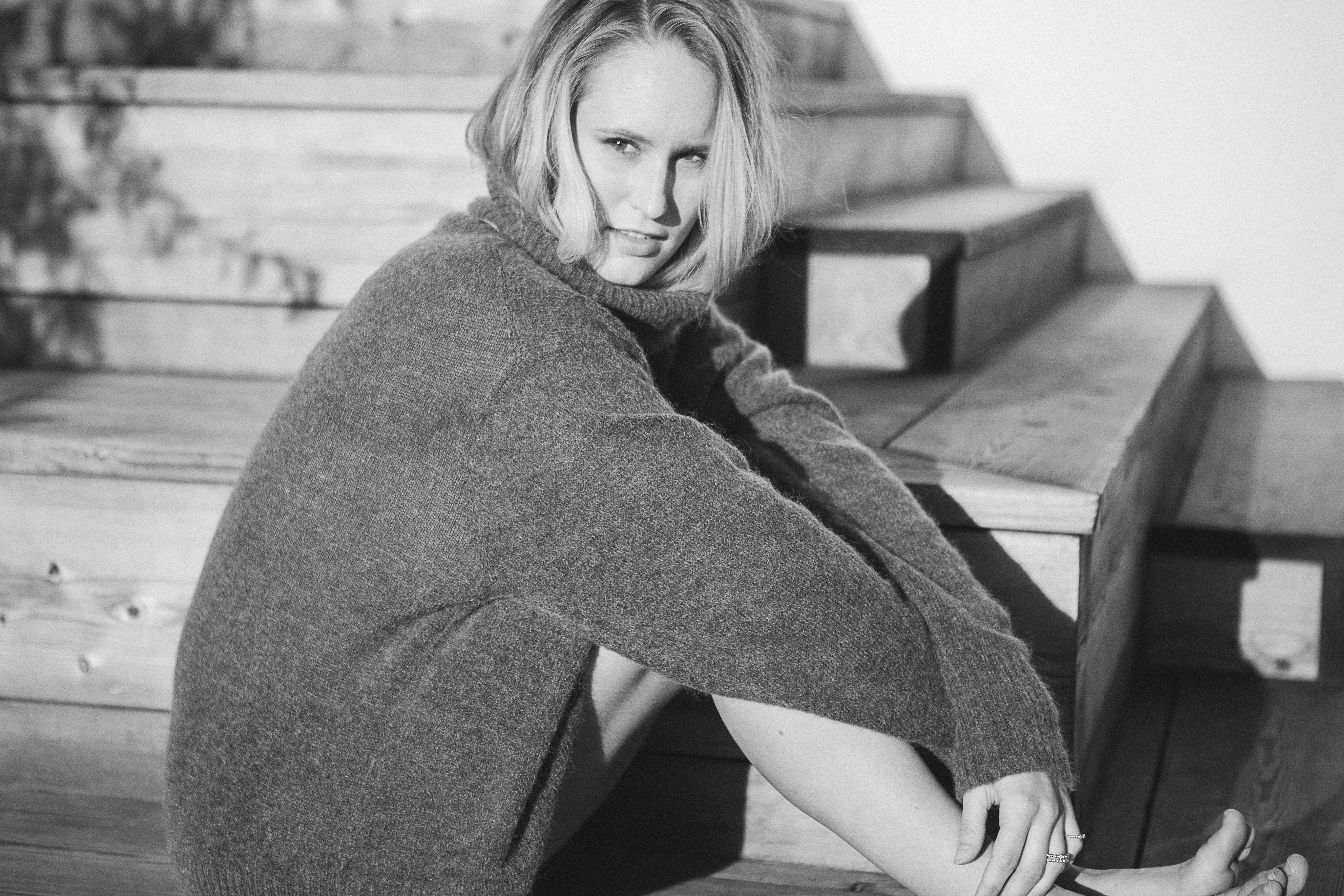 A black-and-white woman in a large sweater sits aside wooden stairs