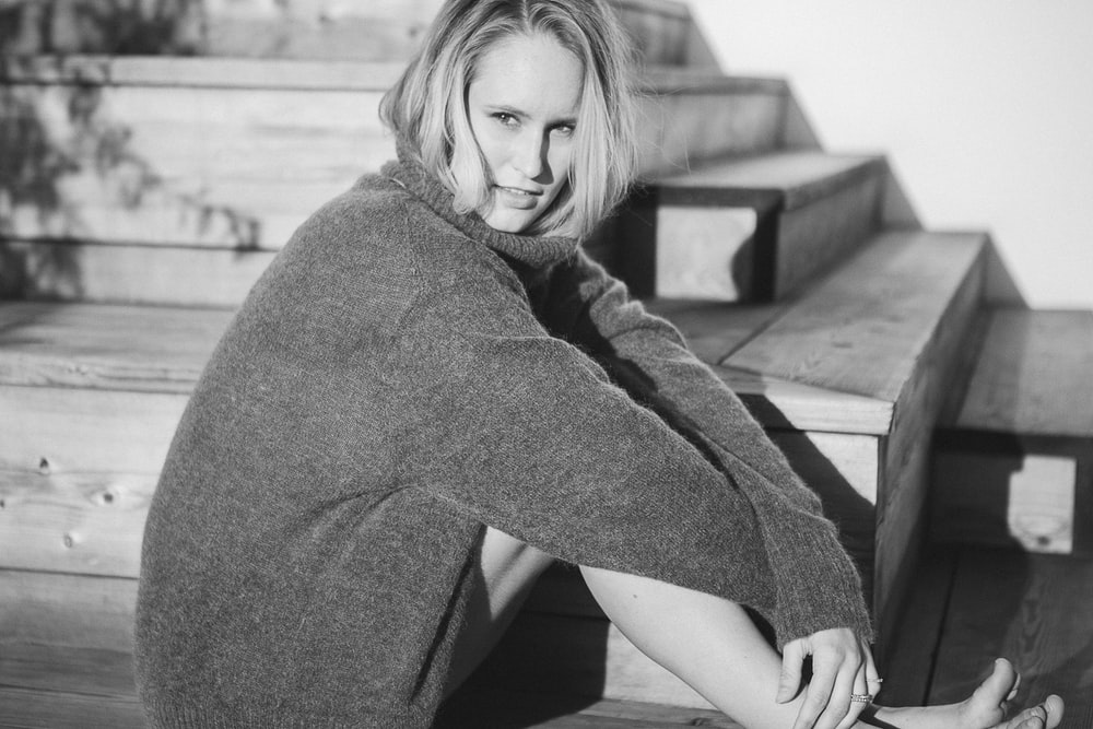 woman wearing cardigan sitting on stairs
