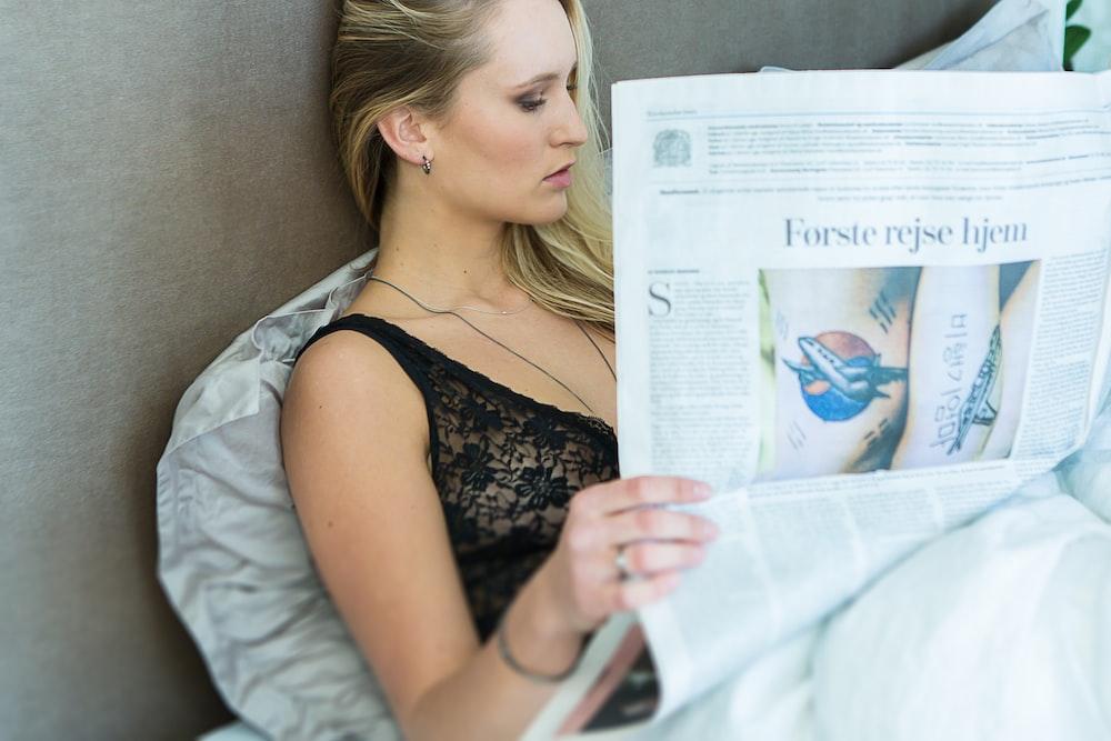 woman wearing black chemise reading newspaper