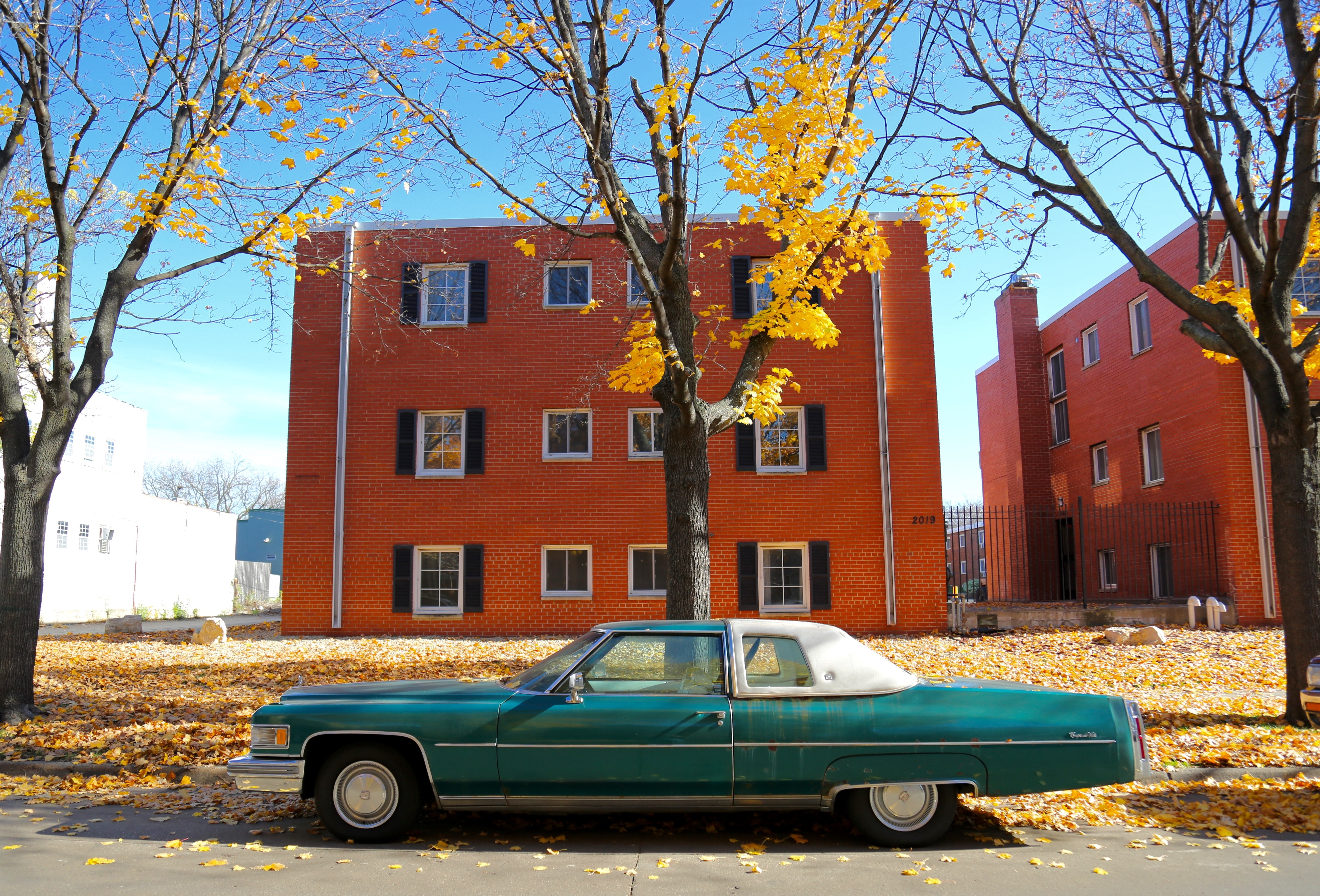 Vintage cyan car parked on a street in front of a brick building in autumn