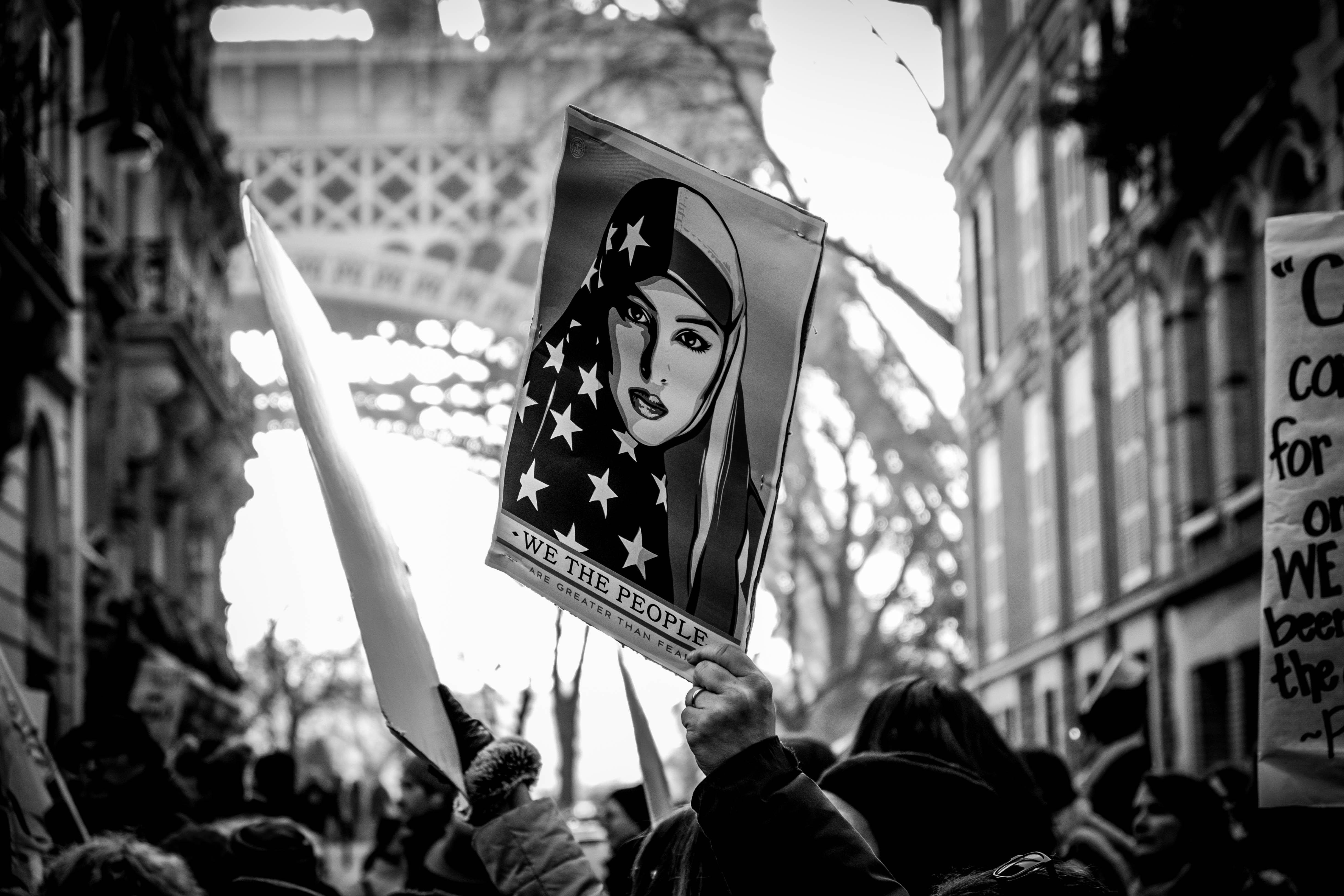 """A person holding up a """"We the people"""" sign at a protest near the Eiffel Tower"""