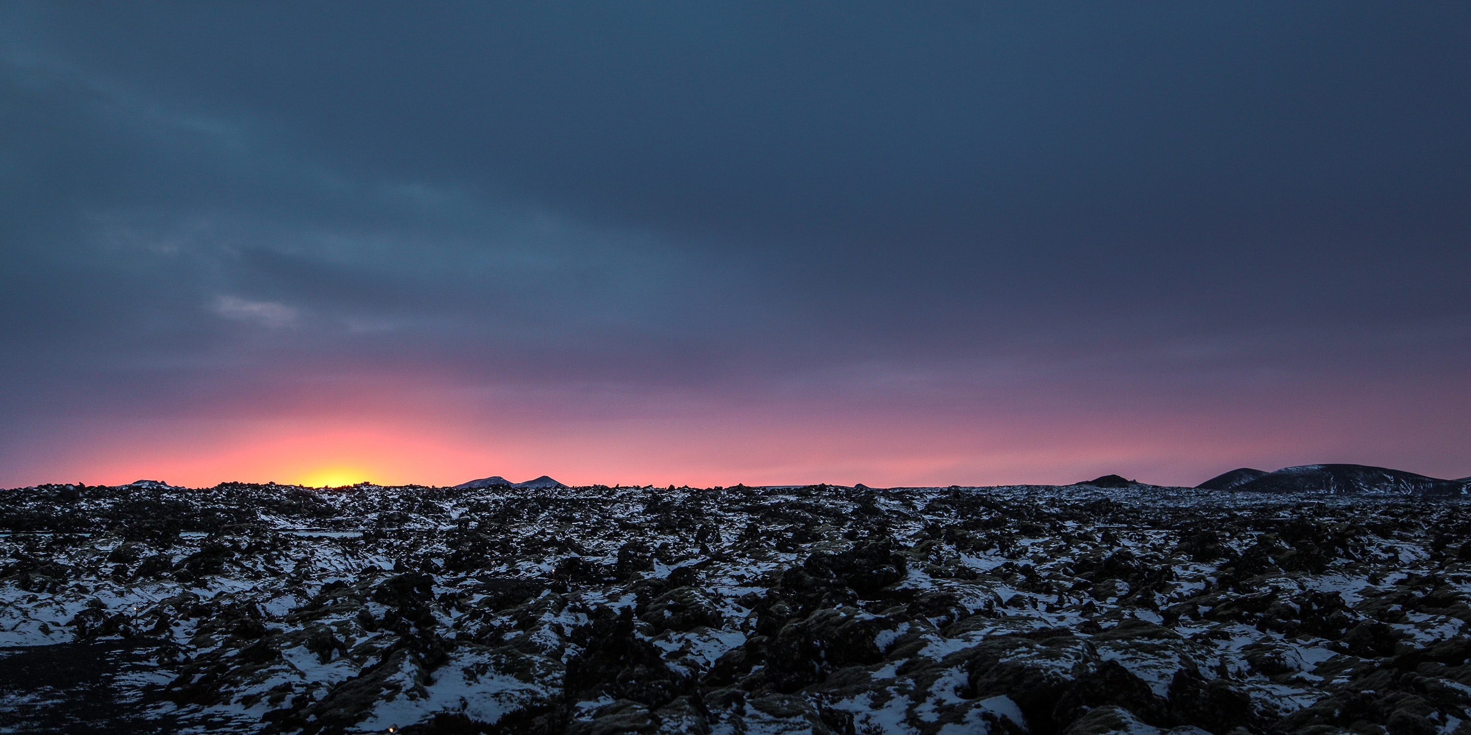 The sun just below horizon on a rocky landscape with light snow