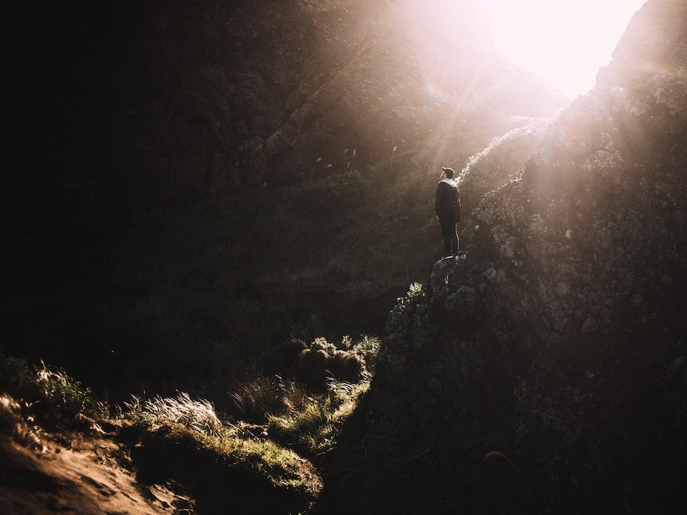 man standing on rock mountain during daytime