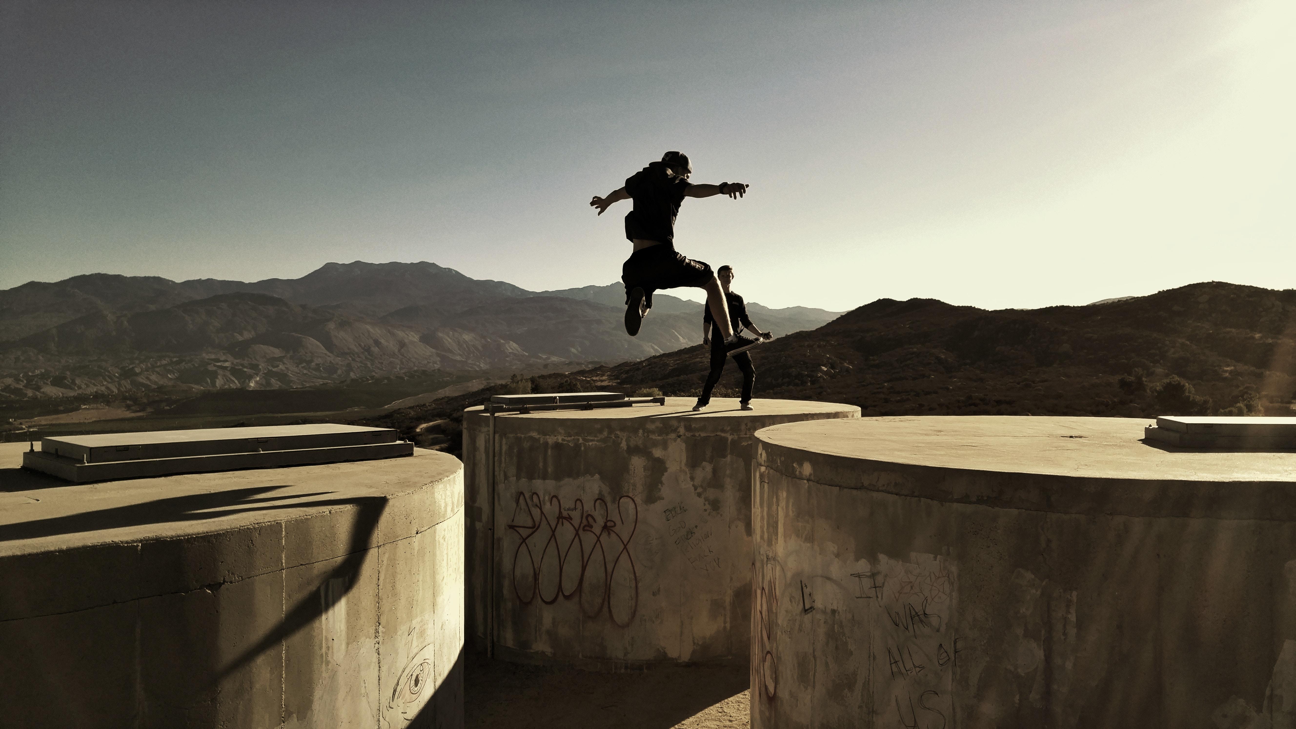 man jumping between two cylinder buldings