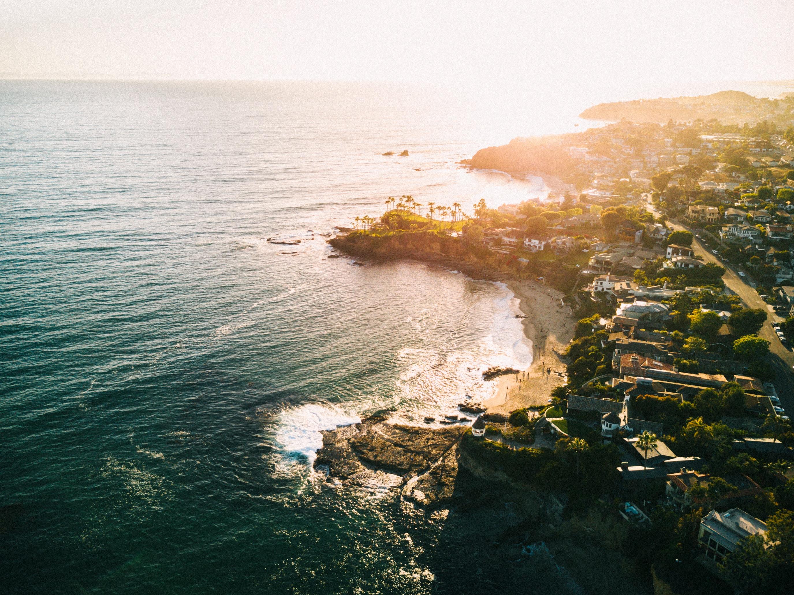 Drone aerial view of the urban Laguna Beach coastline at sunset