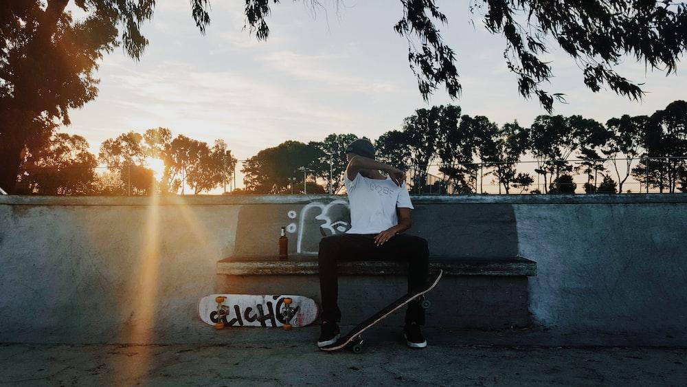 man sitting on chair beside white skateboard