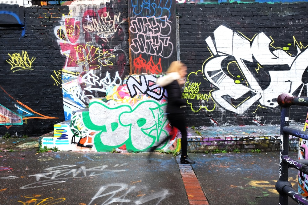 panning photography of woman walking beside wall with graffiti art