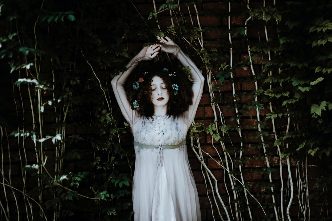 A woman wearing heavy make-up lifting her hands up near an ivy-covered wall