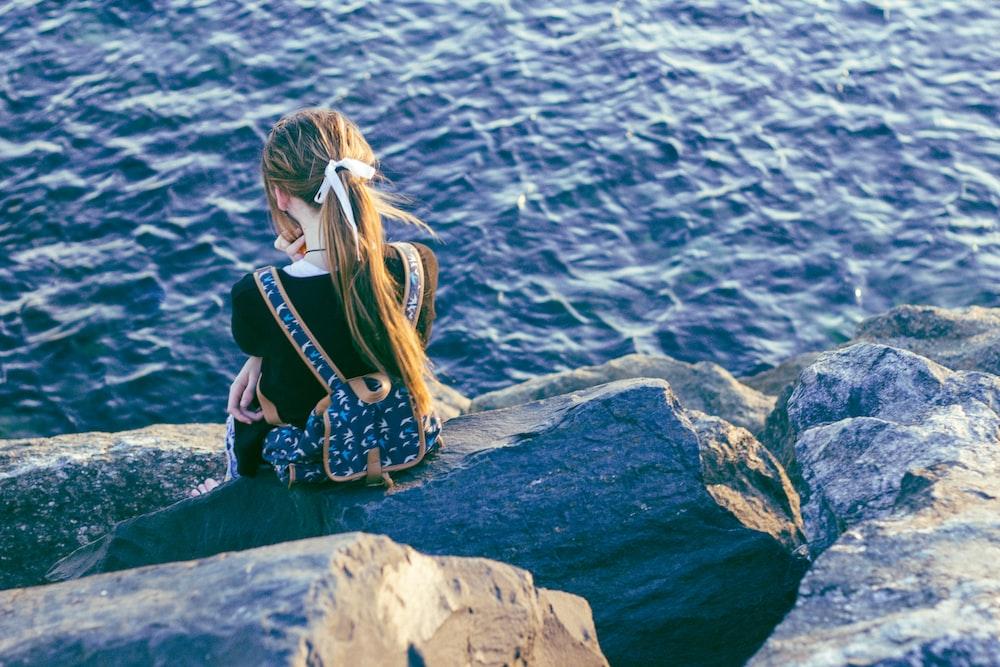girl sitting on gray rocks