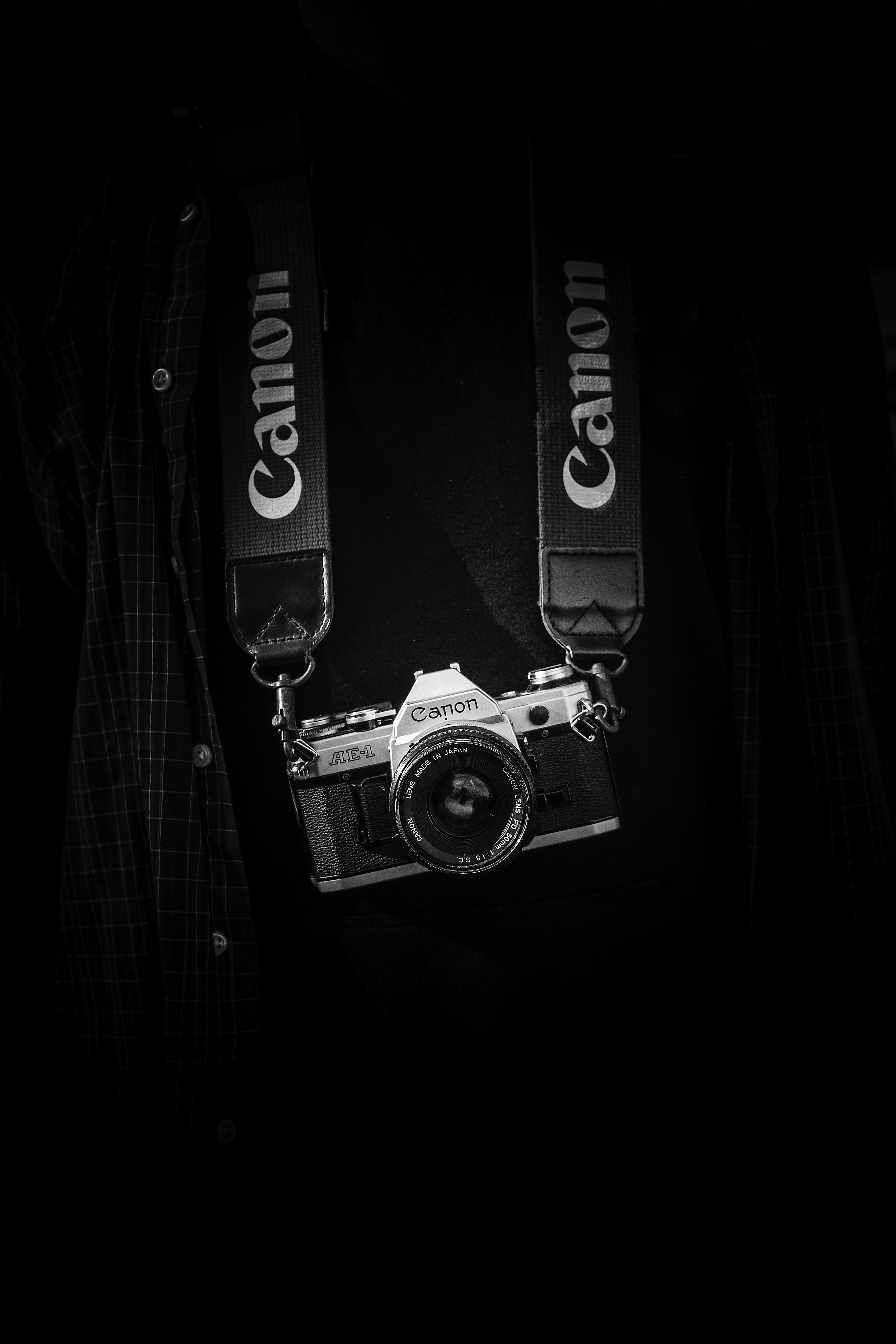 Black and white shot of canon camera with strap on torso with checked shirt