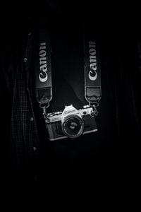 gray and black Canon camera body with lanyard