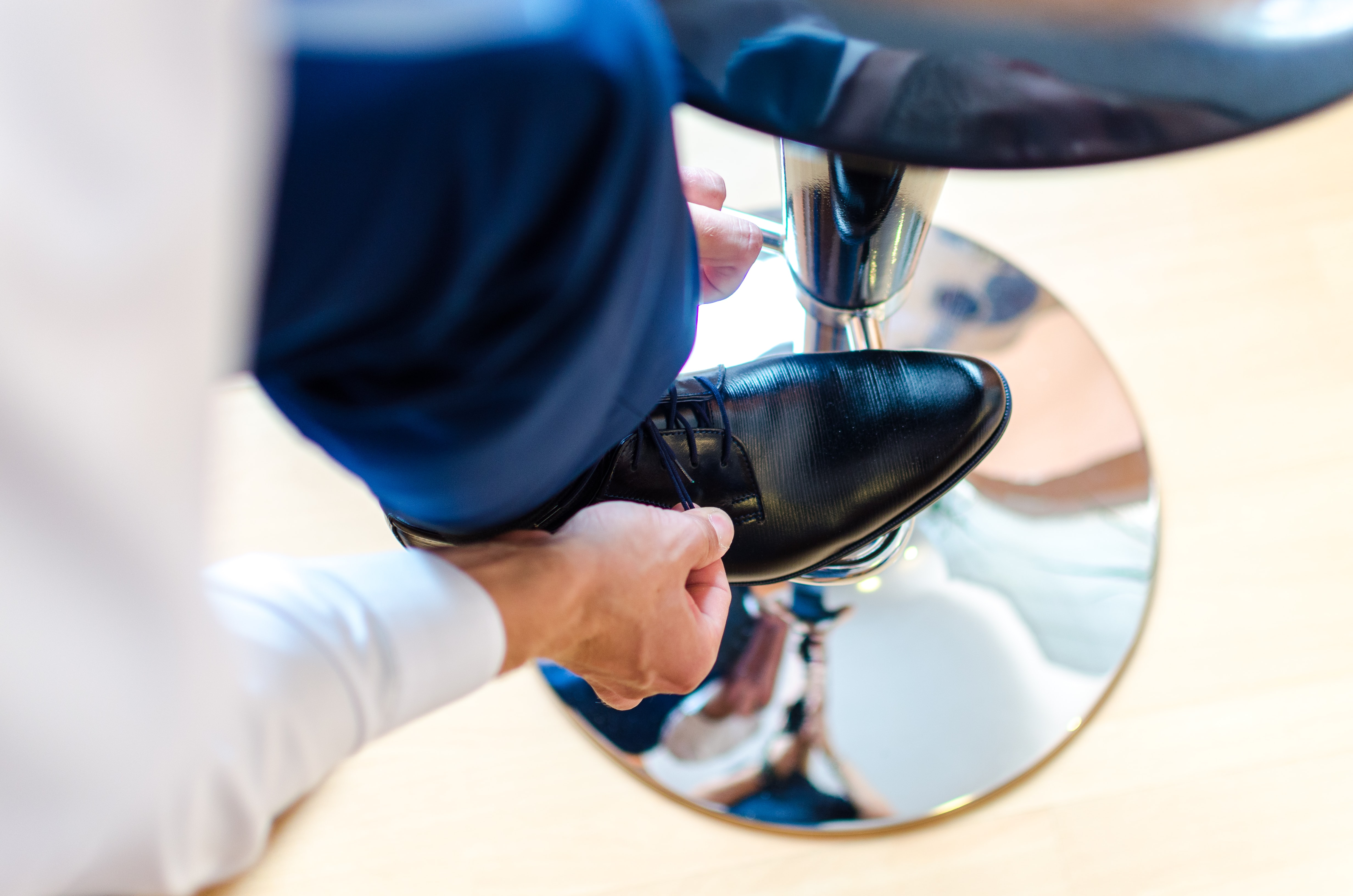A man lacing up his black leather shoes