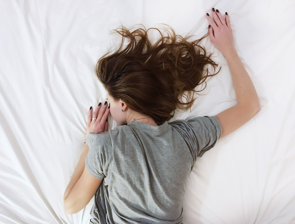 Photo Via: https://unsplash.com/photos/CwIU33KGToc, A woman with brown hair and a gray t-shirt lies face down on a white sheet