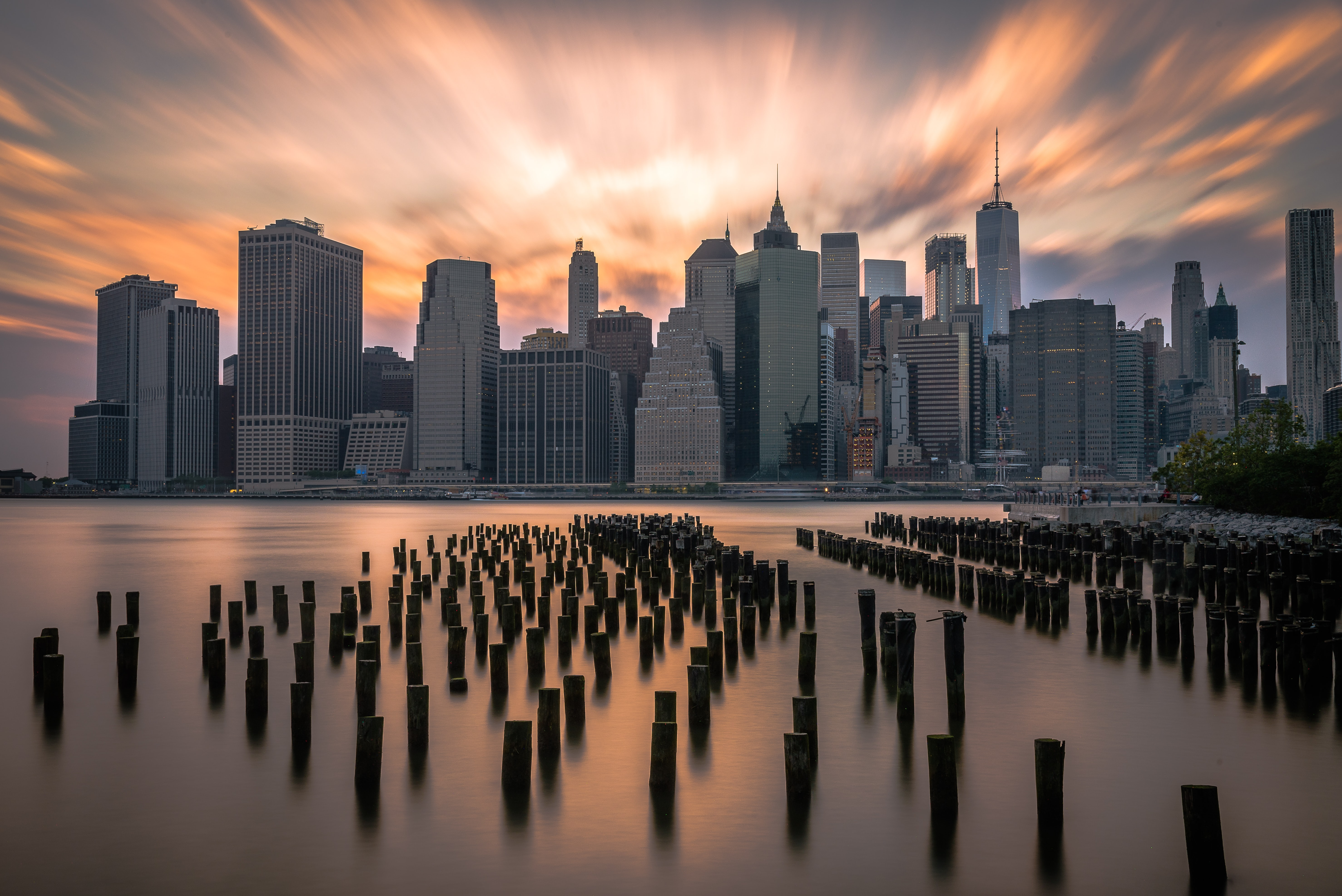 New York City from the Hudson River with the skyline and Freedom Tower in the background during sunset