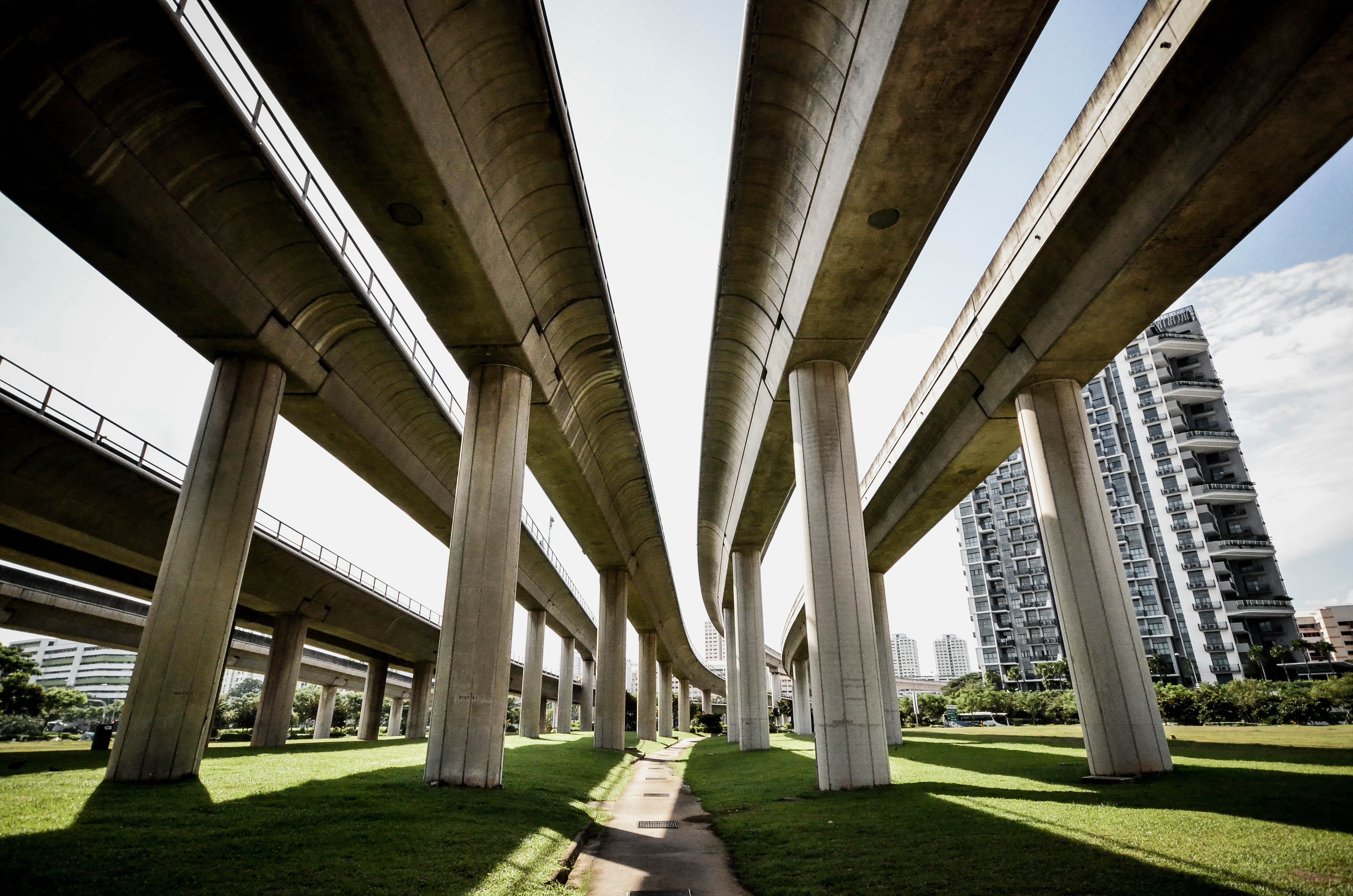 A Singapore freeway and train overpass with skyscraper in the background