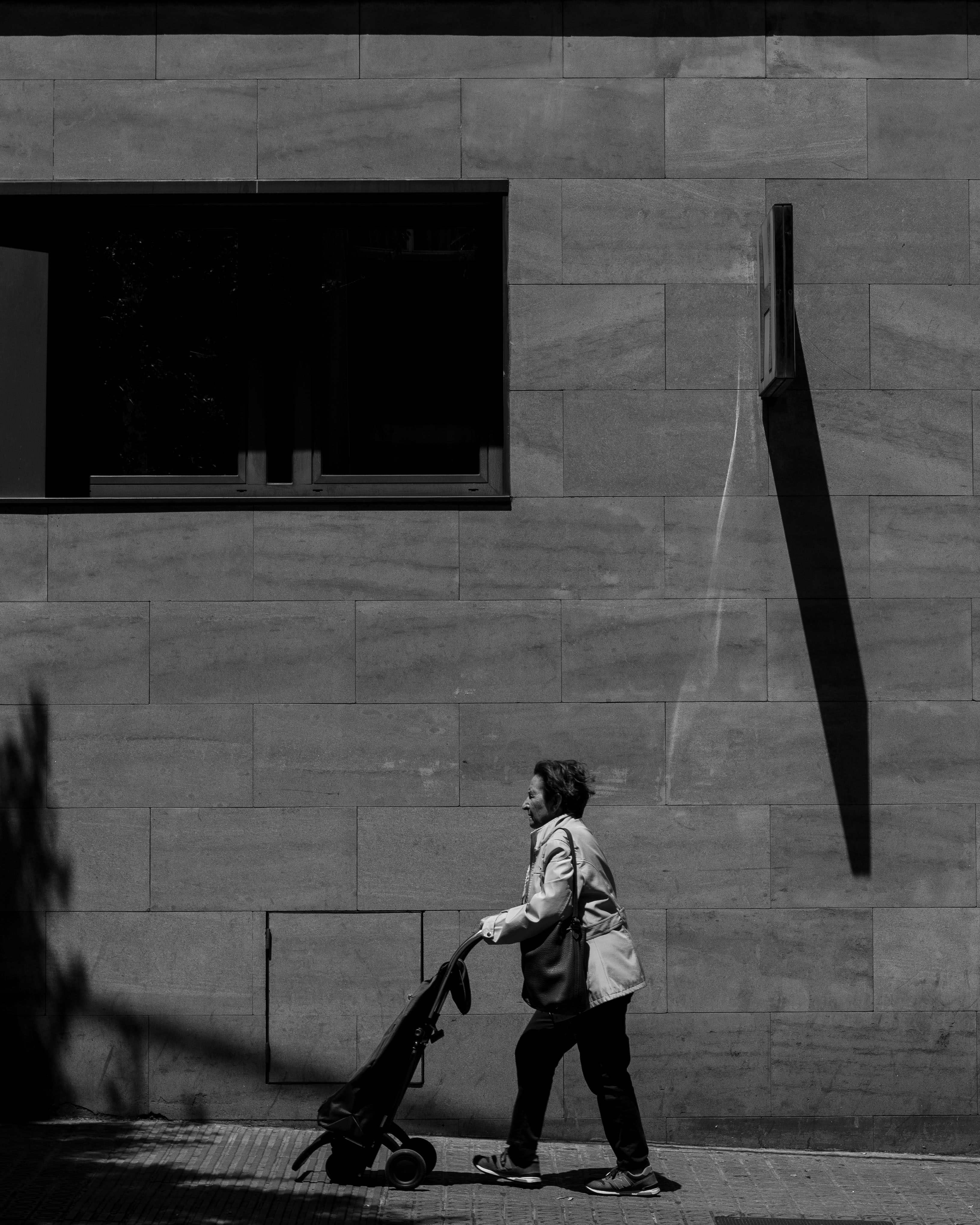 A person in black and white pushes a stroller in front of a wall in Barcelona