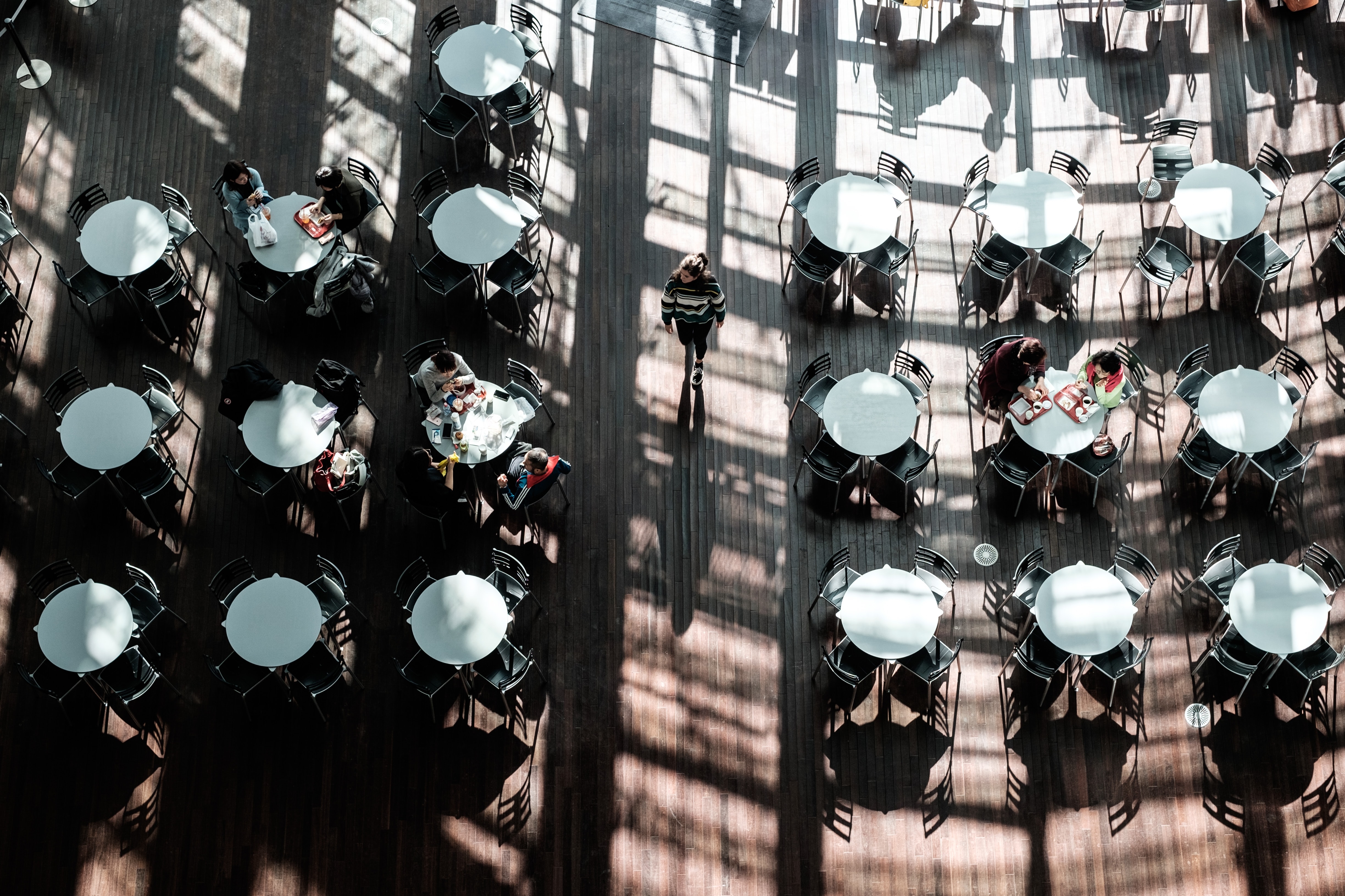 Drone view of people eating at white circular tables with the window casting shadows