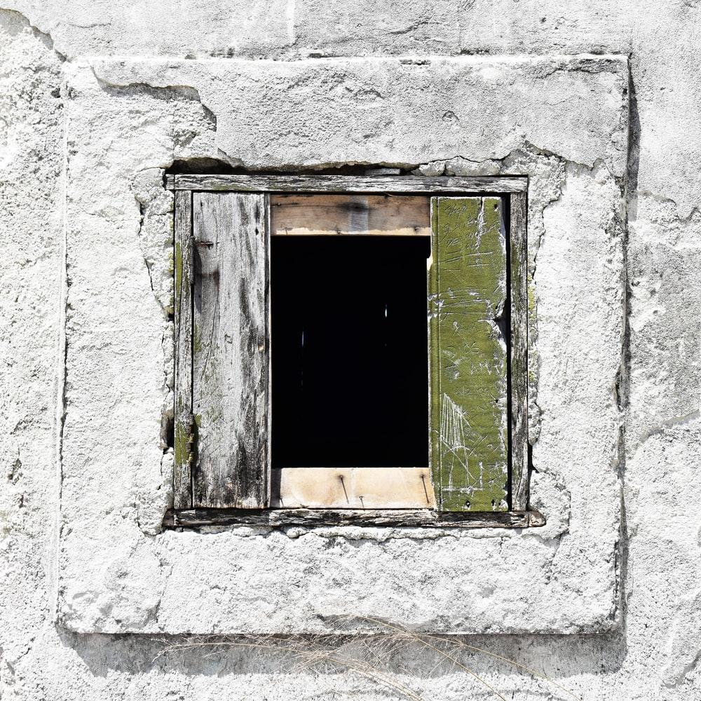 green wooden window on white concrete wall